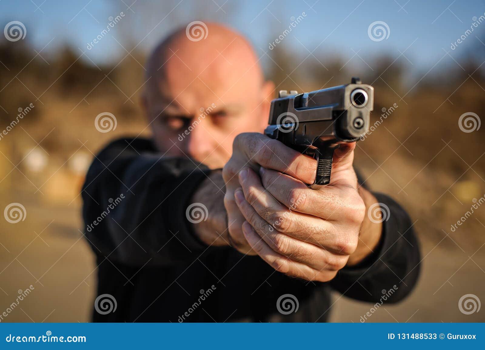 Agente de policía y escolta que señalan la pistola para proteger contra atacante