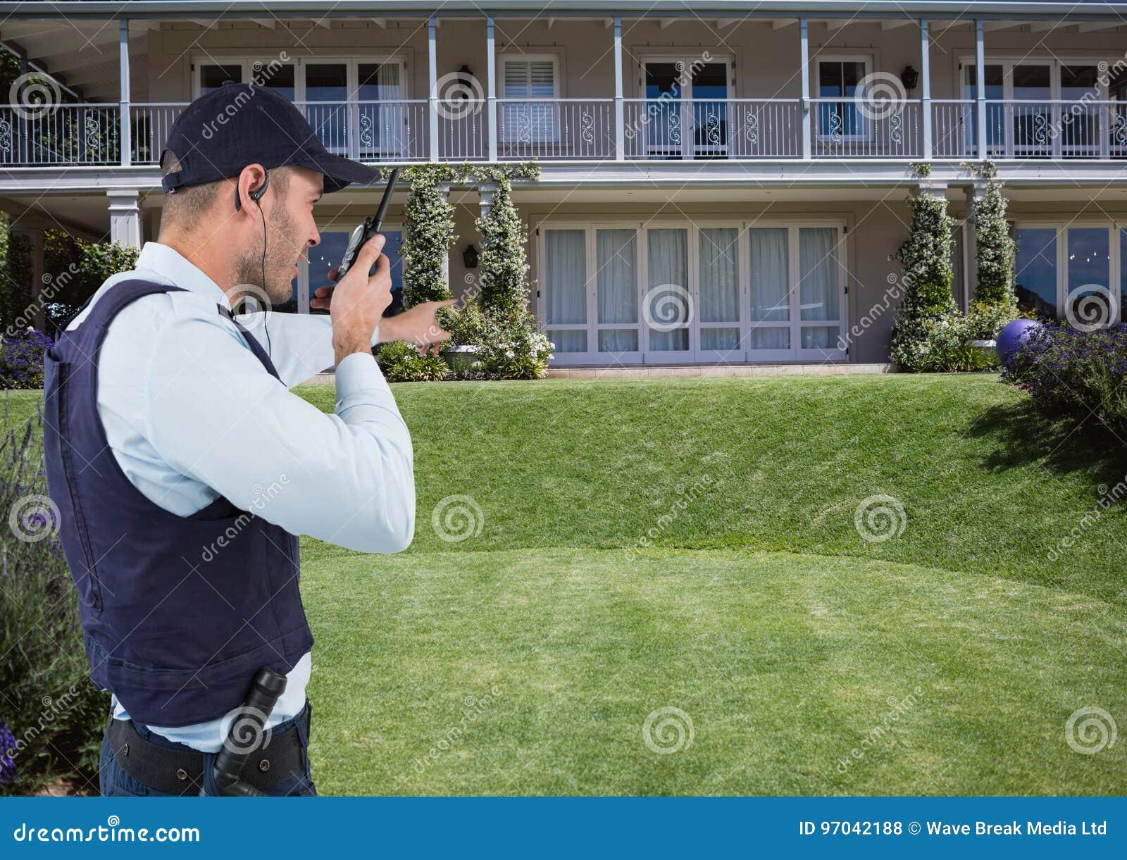 Agente de segurança que fala no rádio ao apontar na casa