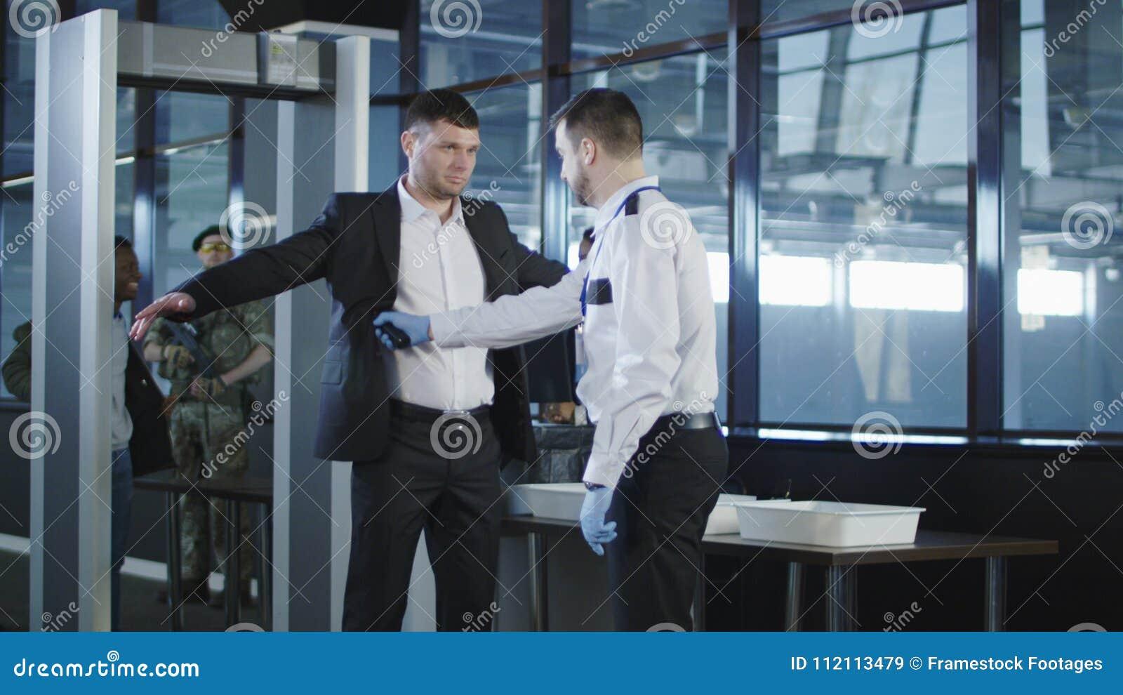 Agente de seguridad que usa un detector de metales en un hombre