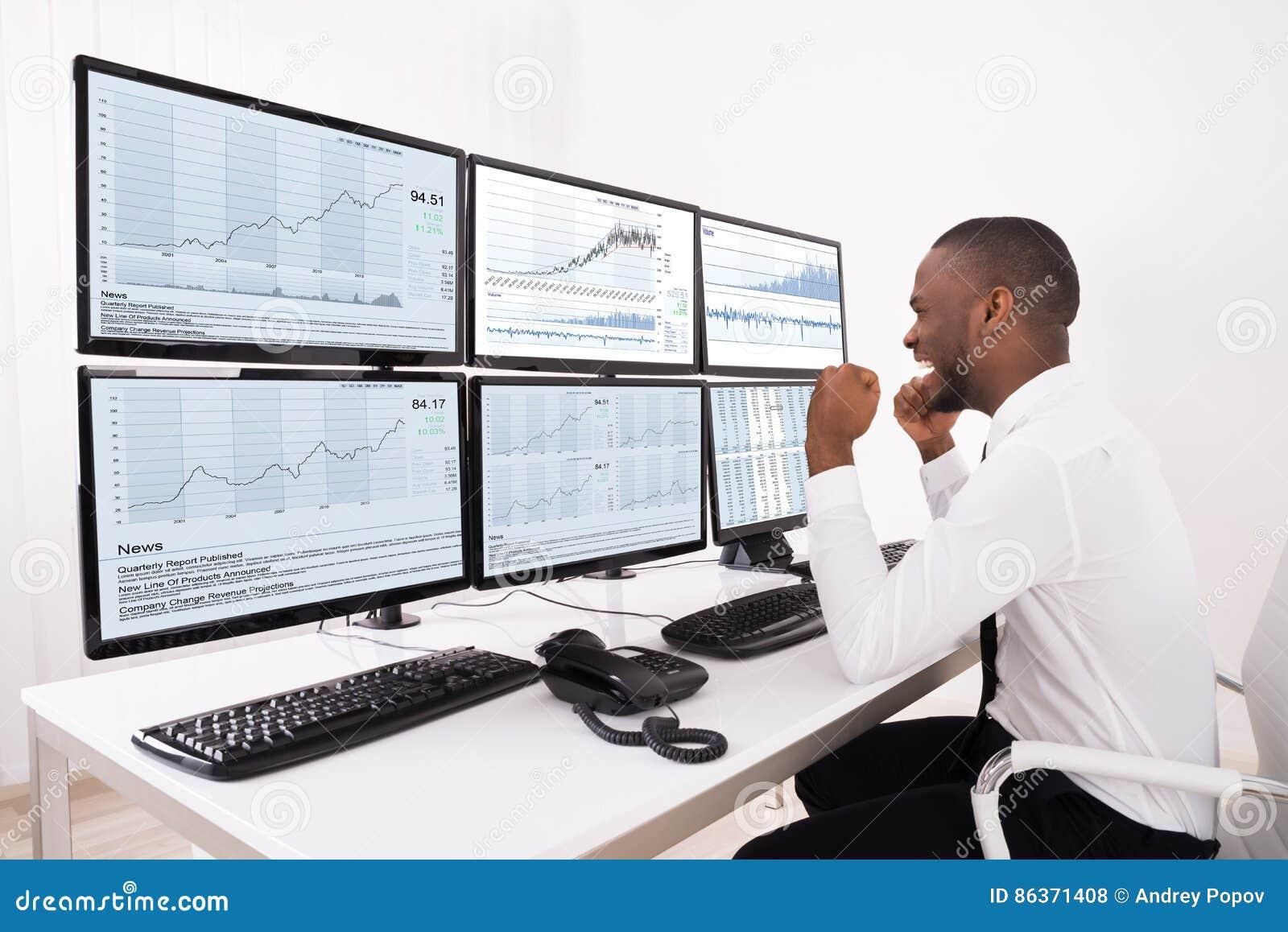 Agente feliz Looking At Graphs del mercado de acción en el ordenador múltiple