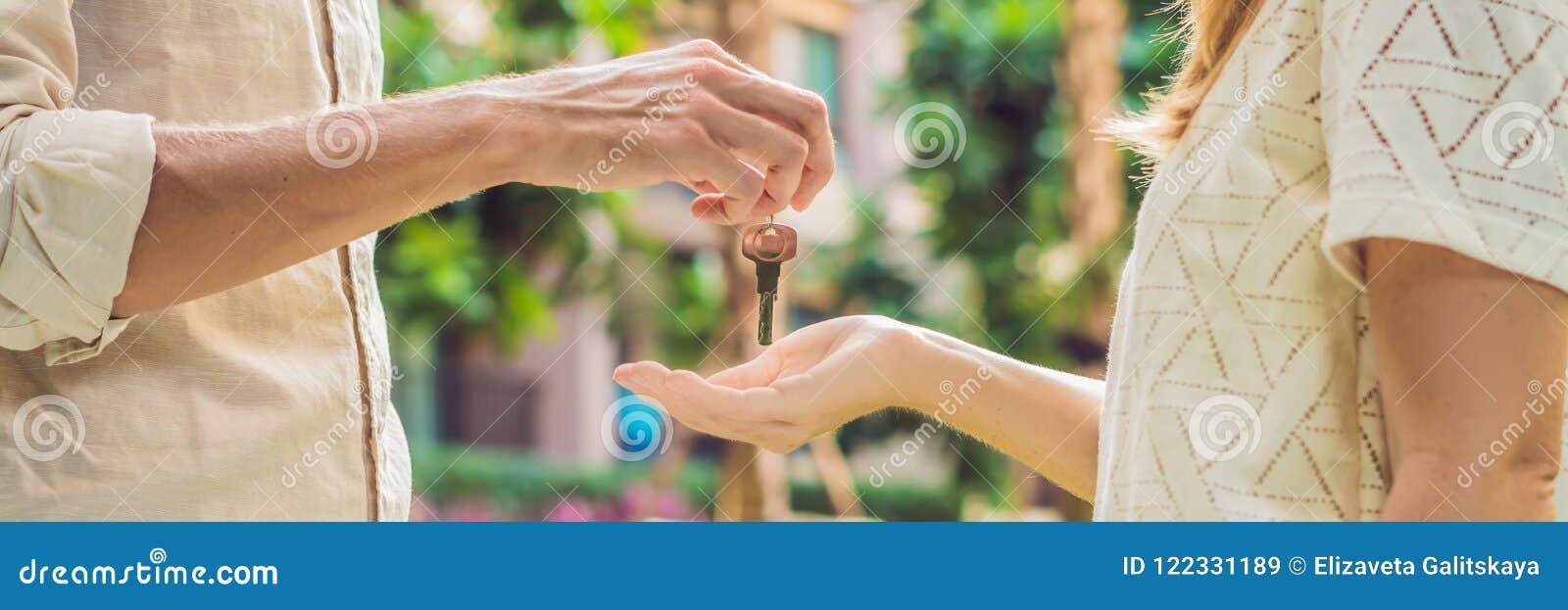 Agente immobiliare che fornisce le chiavi al proprietario dell appartamento, comprante vendendo affare della proprietà Chiuda su