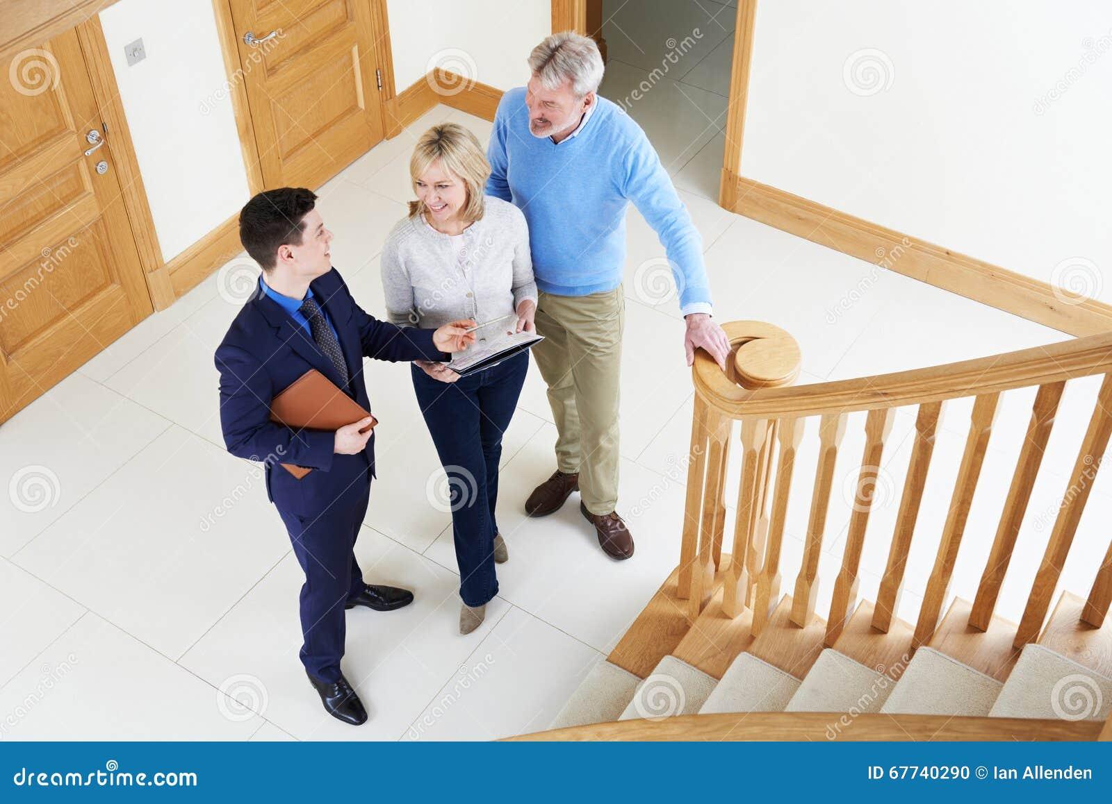 Agente inmobiliario que muestra pares maduros alrededor de la casa para la venta