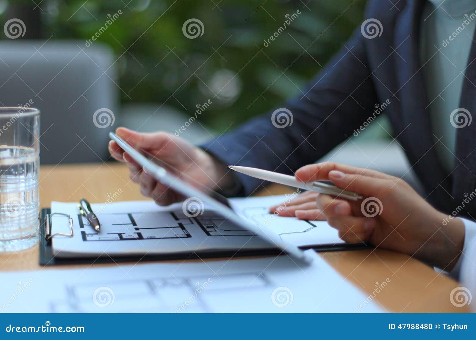 Agente inmobiliario que muestra planes de la casa