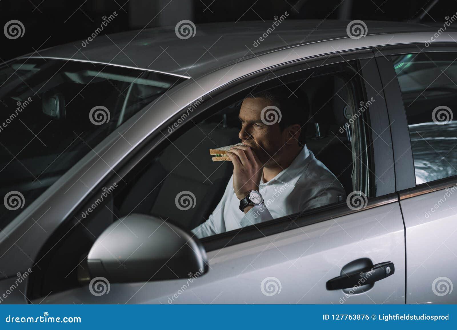 Agente investigativo privato maschio che mangia panino