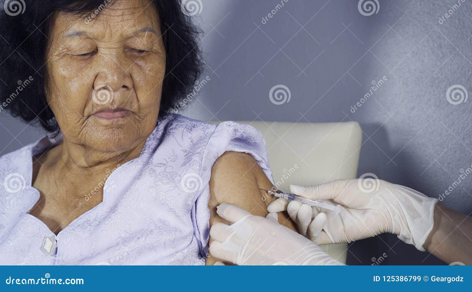 Aggiusti fare l iniezione vaccino nella donna senior