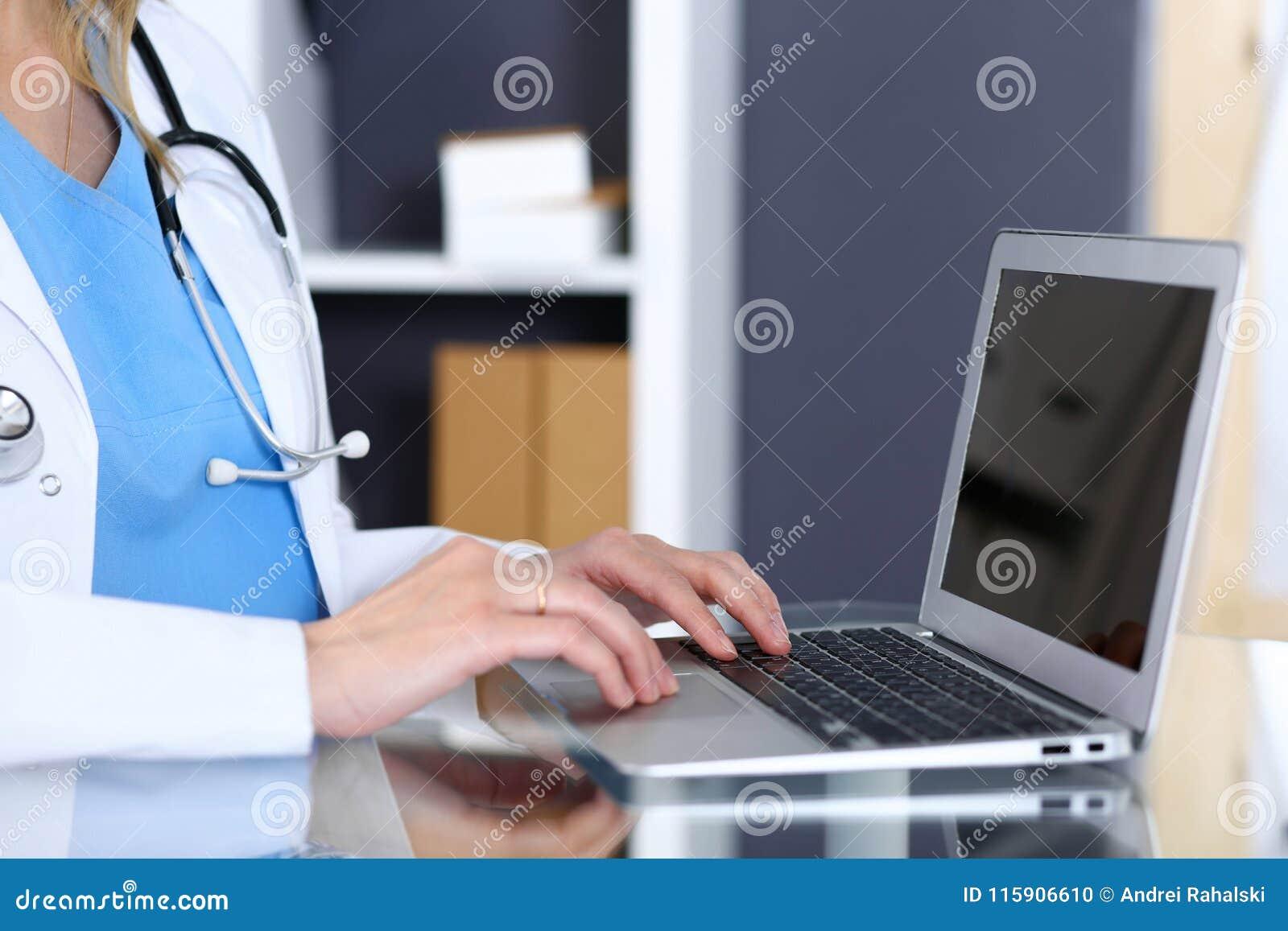 Aggiusti la battitura a macchina sul computer portatile mentre si siedono allo scrittorio di vetro nell ufficio dell ospedale Med