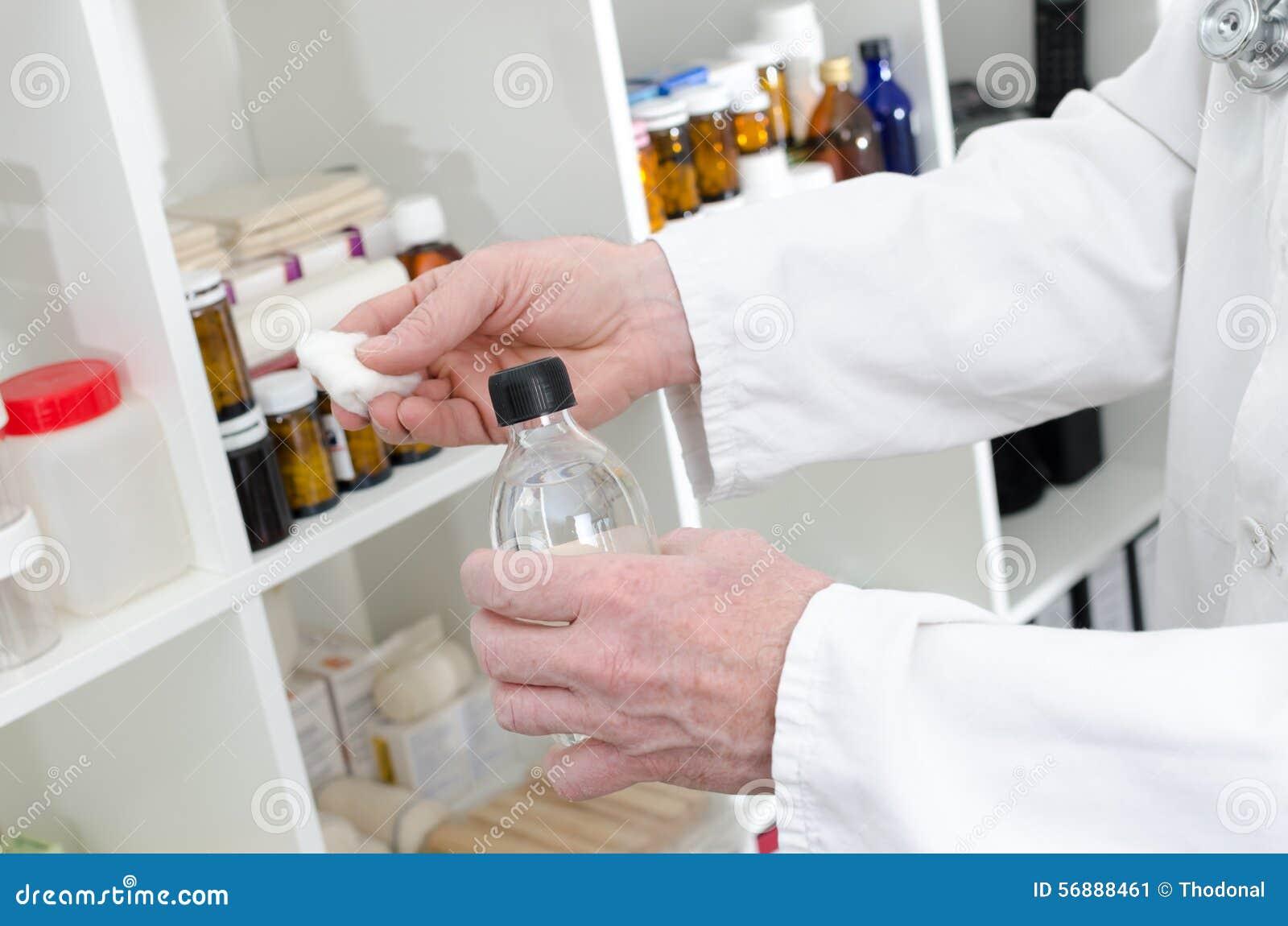Aggiusti la tenuta una bottiglia del disinfettante e del pezzo di cotone