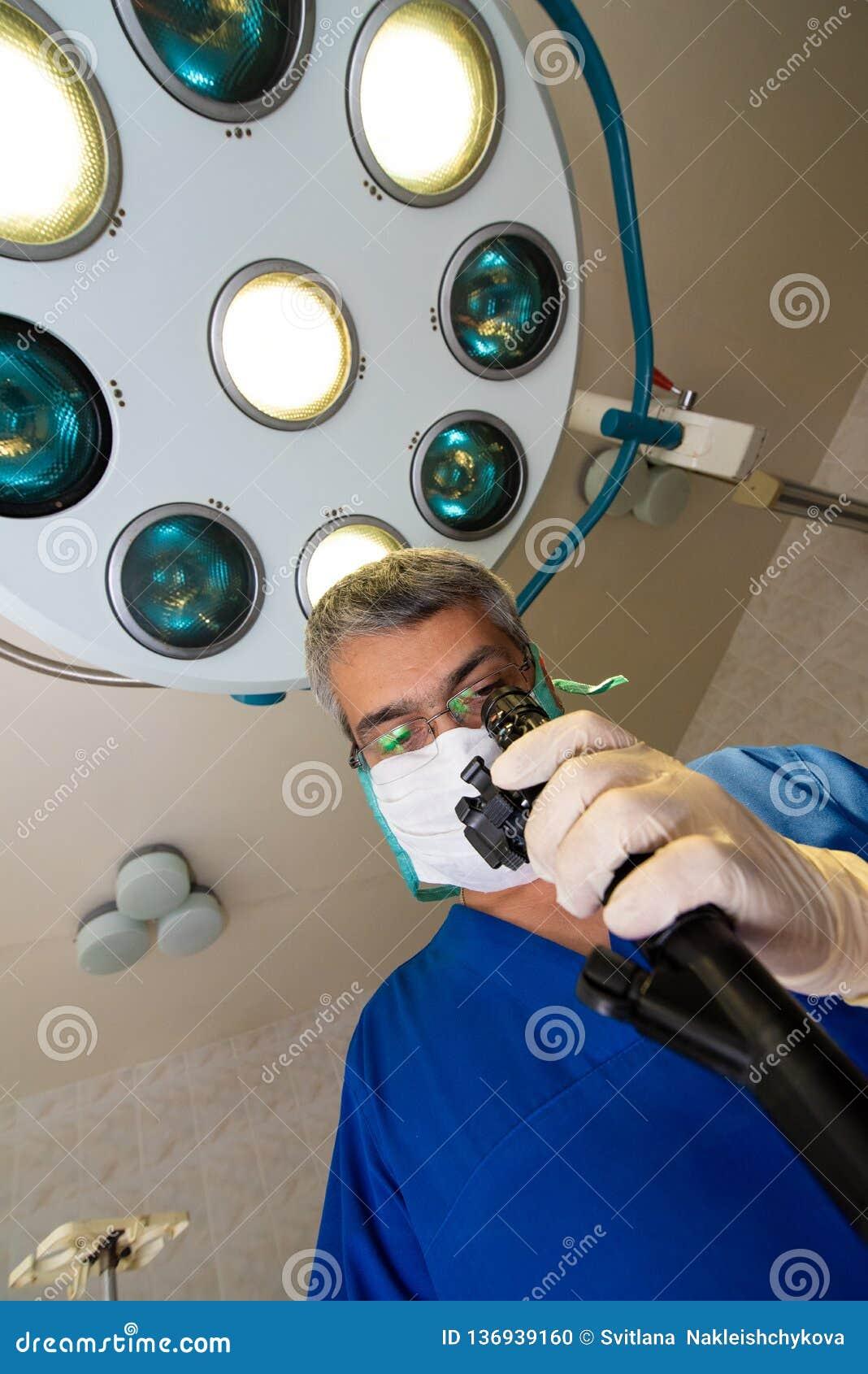 Aggiusti in un abito blu e negli sguardi della maschera al dispositivo
