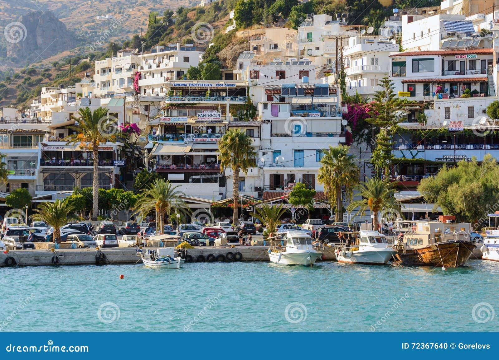 Aghia Galini镇PHarbour有停放的渔船和美丽的房子的在克利特海岛的岩石的