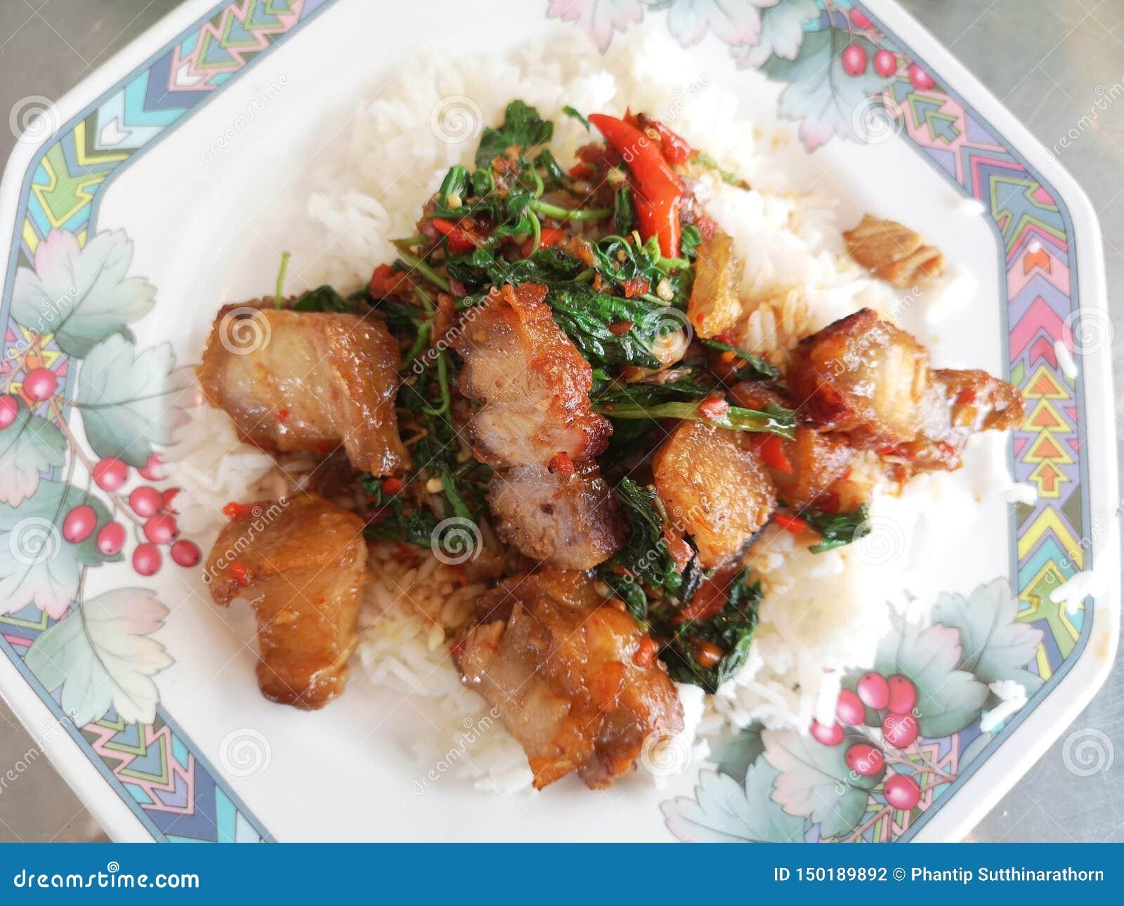 Agitaci?n Fried Spicy Crispy Pork con albahaca tailandesa
