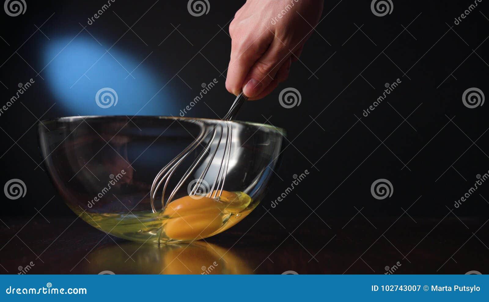 Agitar eggs em uma bacia de vidro com uma suiça
