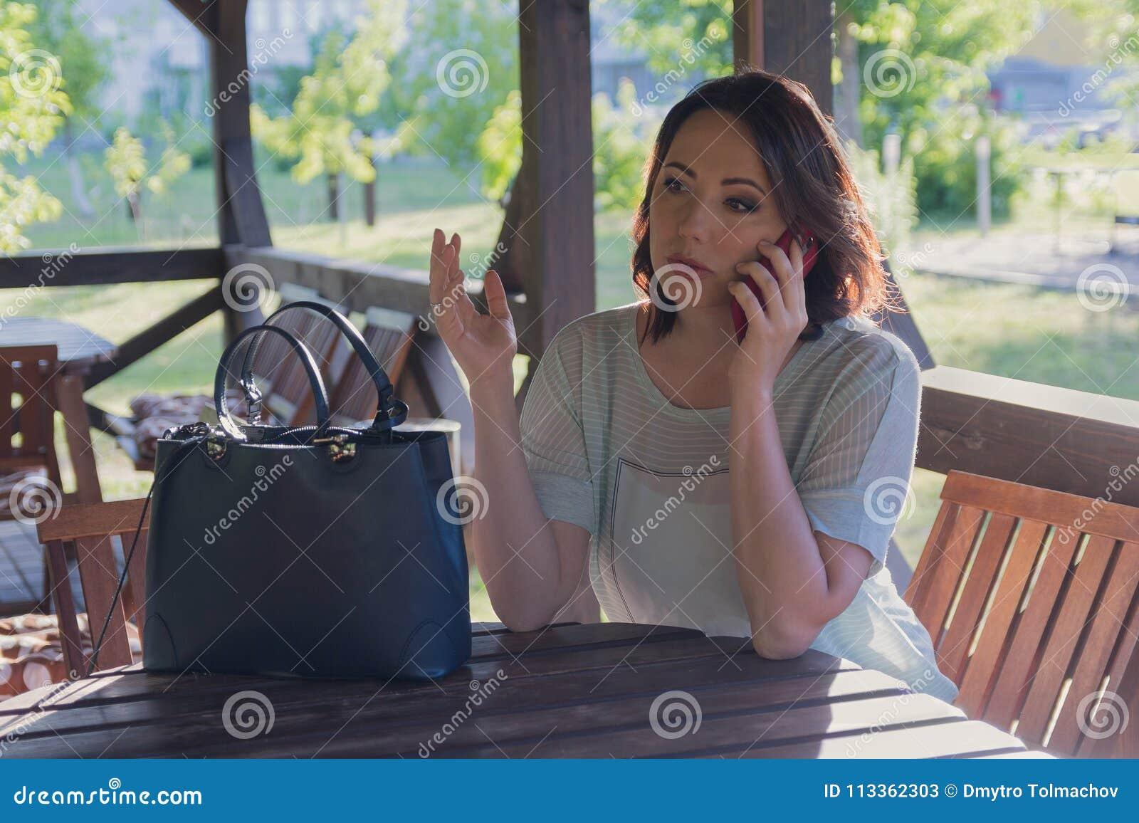 Agitated женщина говорит на smartphone в газебо кафа улицы