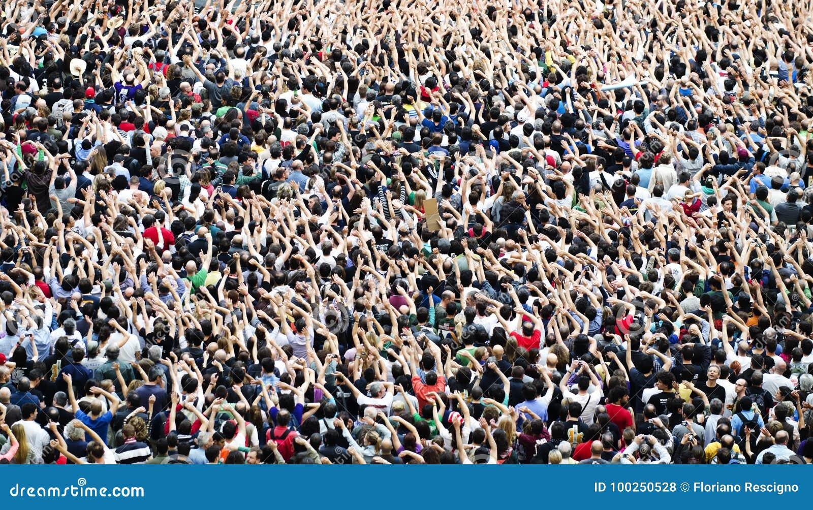 Aglomere-se em um concerto da música, audiência que levanta as mãos acima