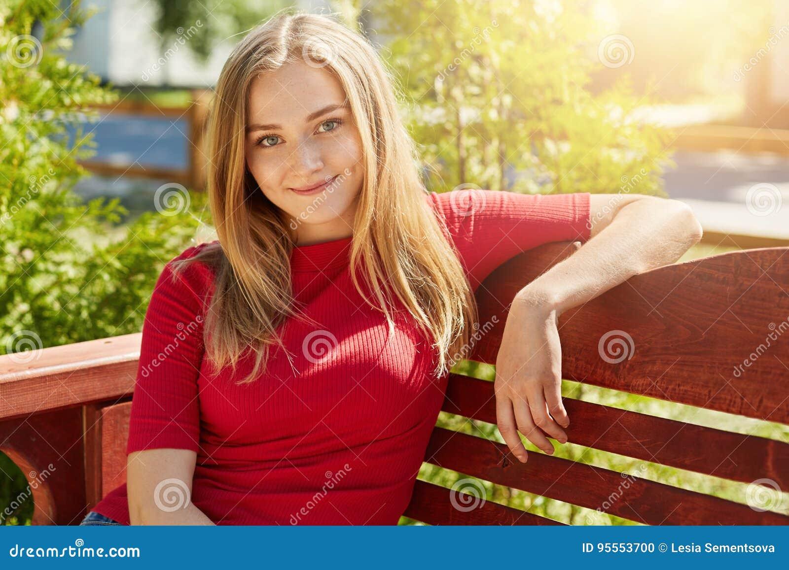 Agradável-olhando a fêmea loura que veste a camiseta vermelha ocasional que senta-se no banco de madeira confortável contra o fun