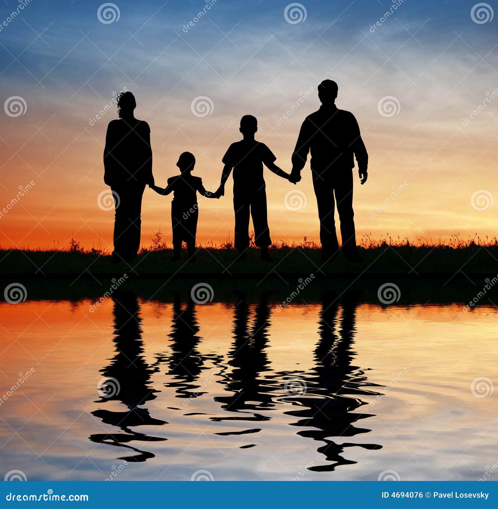 Agregado familiar com quatro membros no céu do por do sol