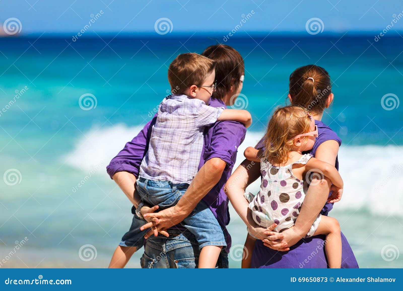 Agregado familiar com quatro membros que olha ao oceano