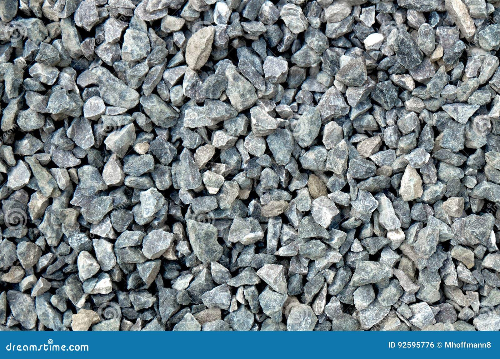 Agregado - piedras gruesas grises claras, machacadas en un hoyo de piedra, modelo de la grava