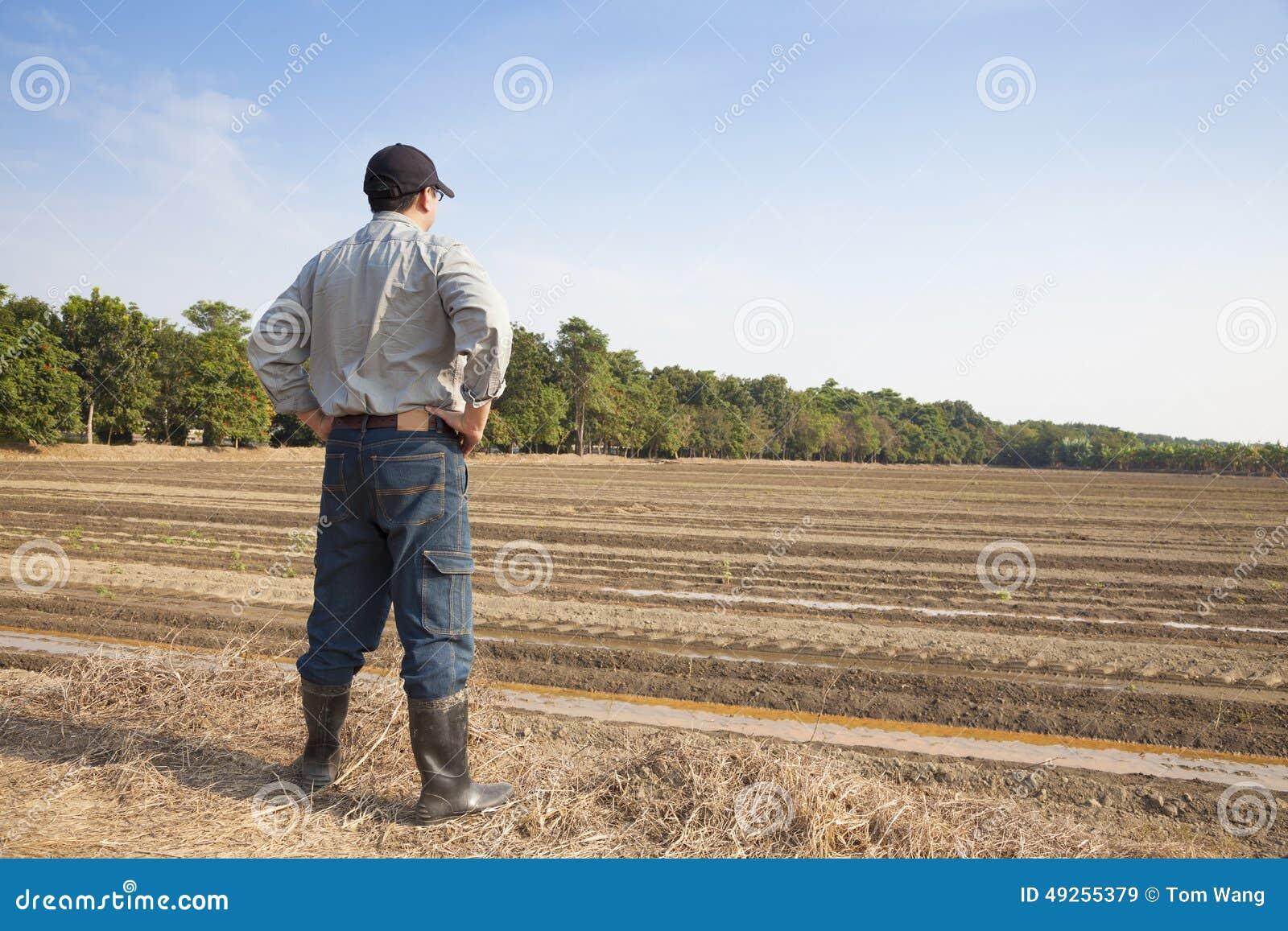 Agricoltore che sta sulla terra di azienda agricola