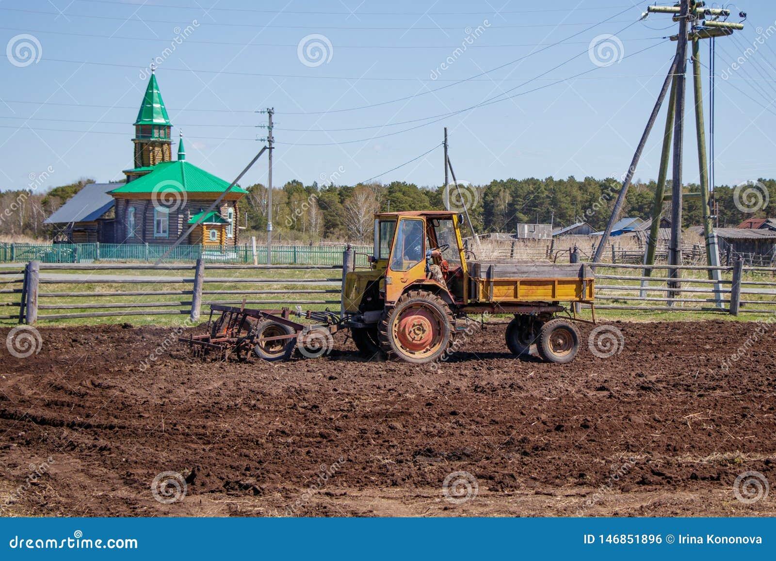 Agriculteur dans le tracteur pr?parant la terre avec le cultivateur de semis
