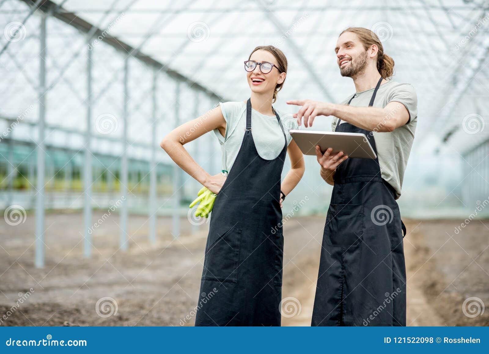 Agriculteurs avec le comprimé dans la serre