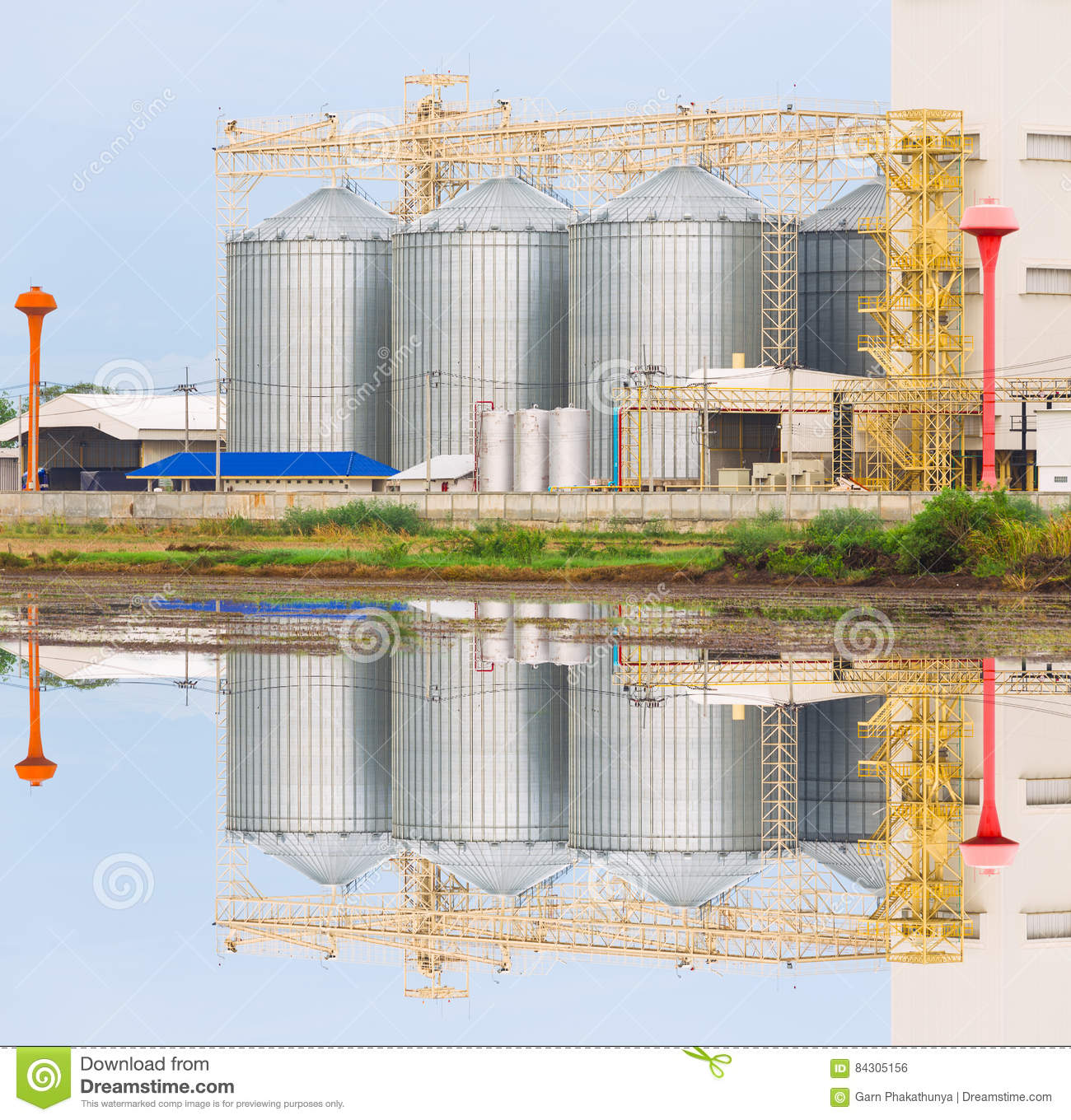 Agricultural Silo - Building Exterior, Storage And Drying Of Grains, Wheat, Corn, Soy, Sunflower Against The Blue Sky With Stock Photo