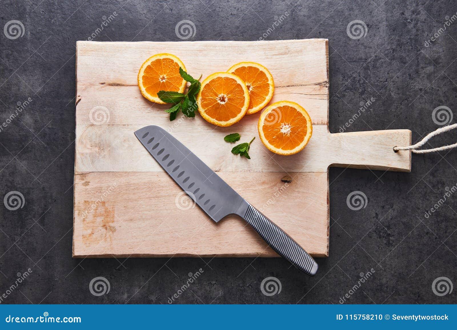 Agrumi freschi, fette arancio del mezzo taglio sul tagliere con il coltello su fondo di pietra scuro, disposizione piana