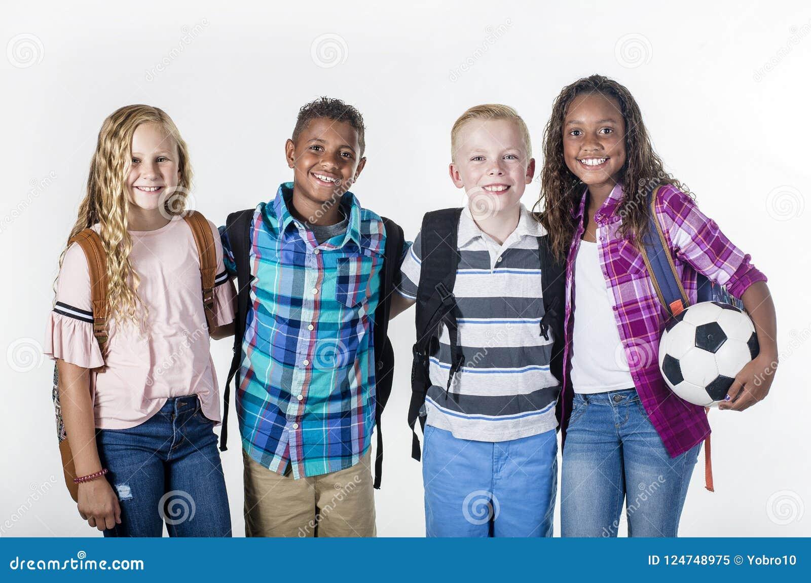 Agrupe el retrato de los niños preadolescentes de la escuela que sonríen en un fondo blanco