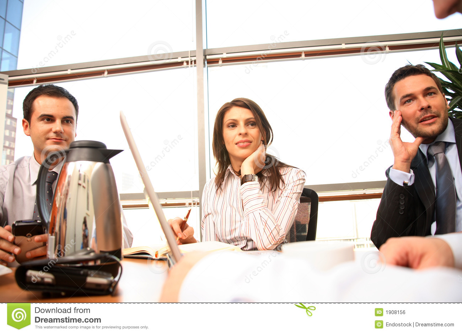 Agrupe a las personas del asunto que trabajan junto con la computadora portátil en oficina asoleada
