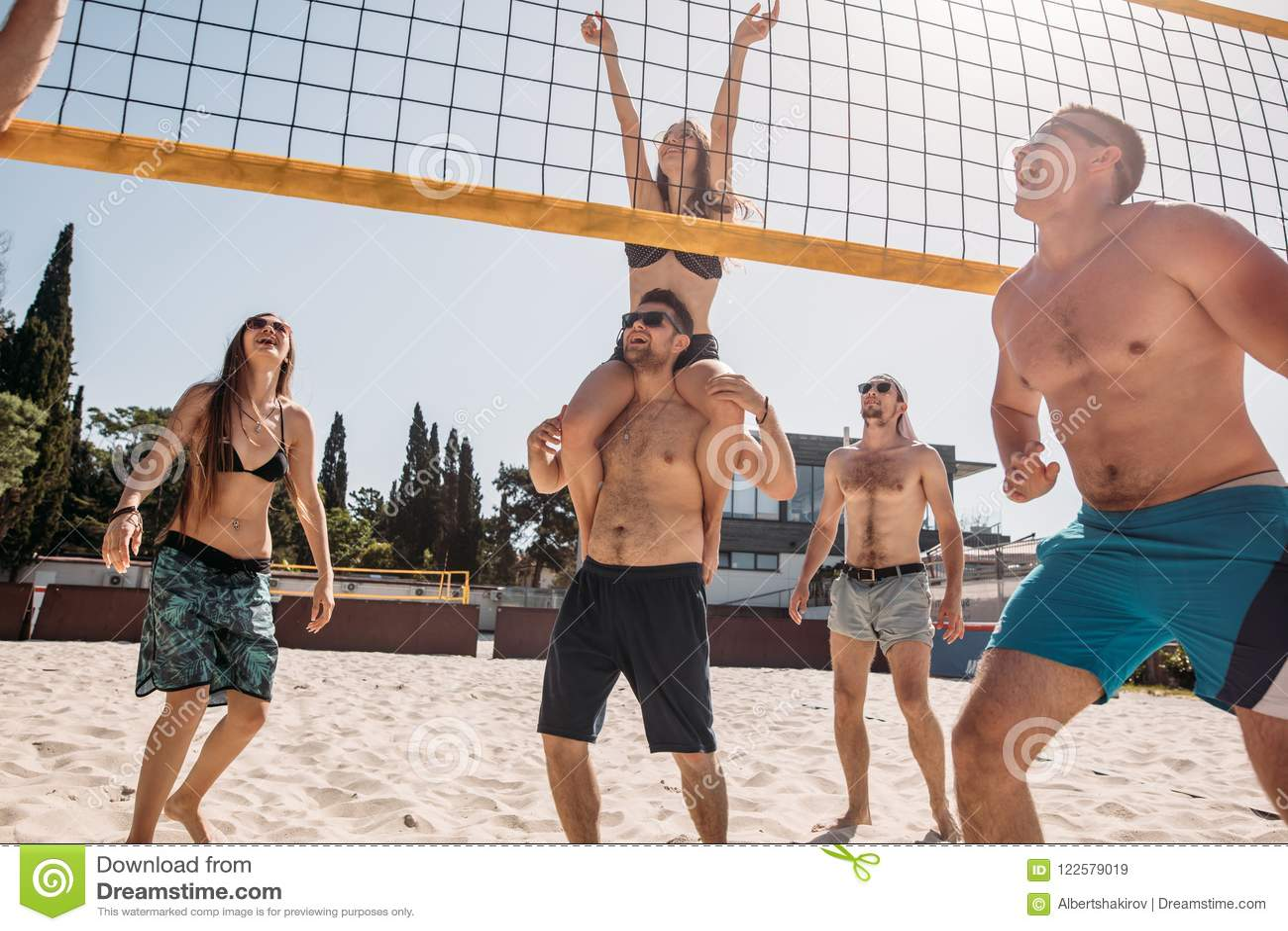 Agrupe a los amigos caucásicos jovenes que juegan a voleibol en la playa el vacaciones de verano