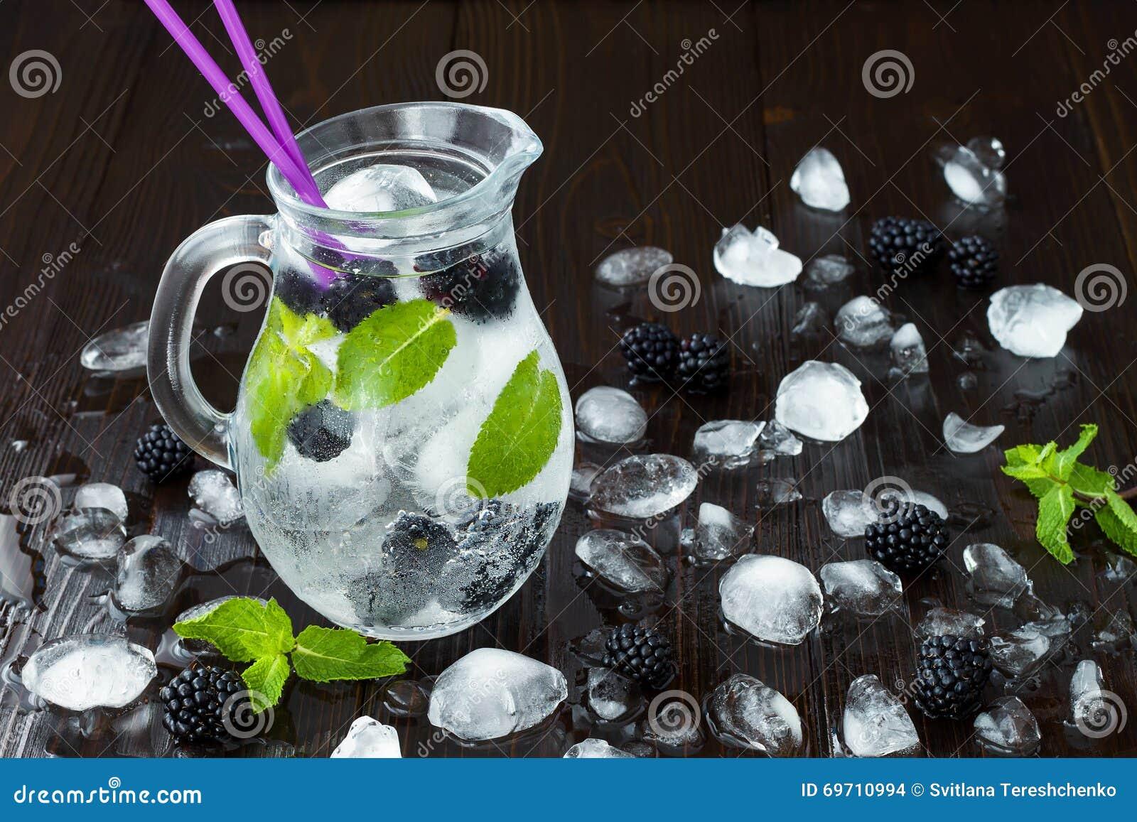 Agua condimentada detox sano con la zarzamora y la menta Bebida de restauración fría de la baya con hielo en la tabla de madera o