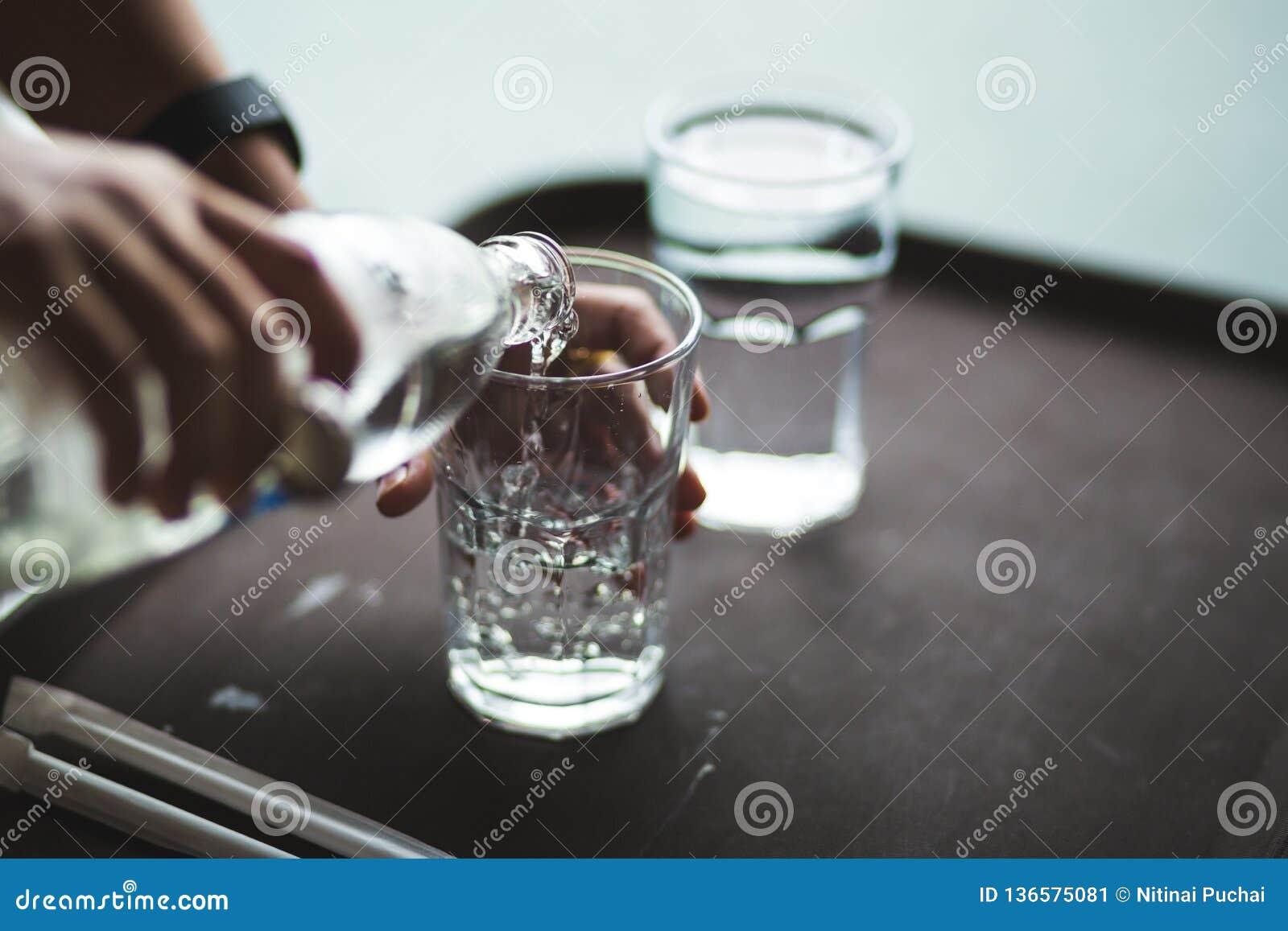 Agua de colada de la mano en una botella de cristal
