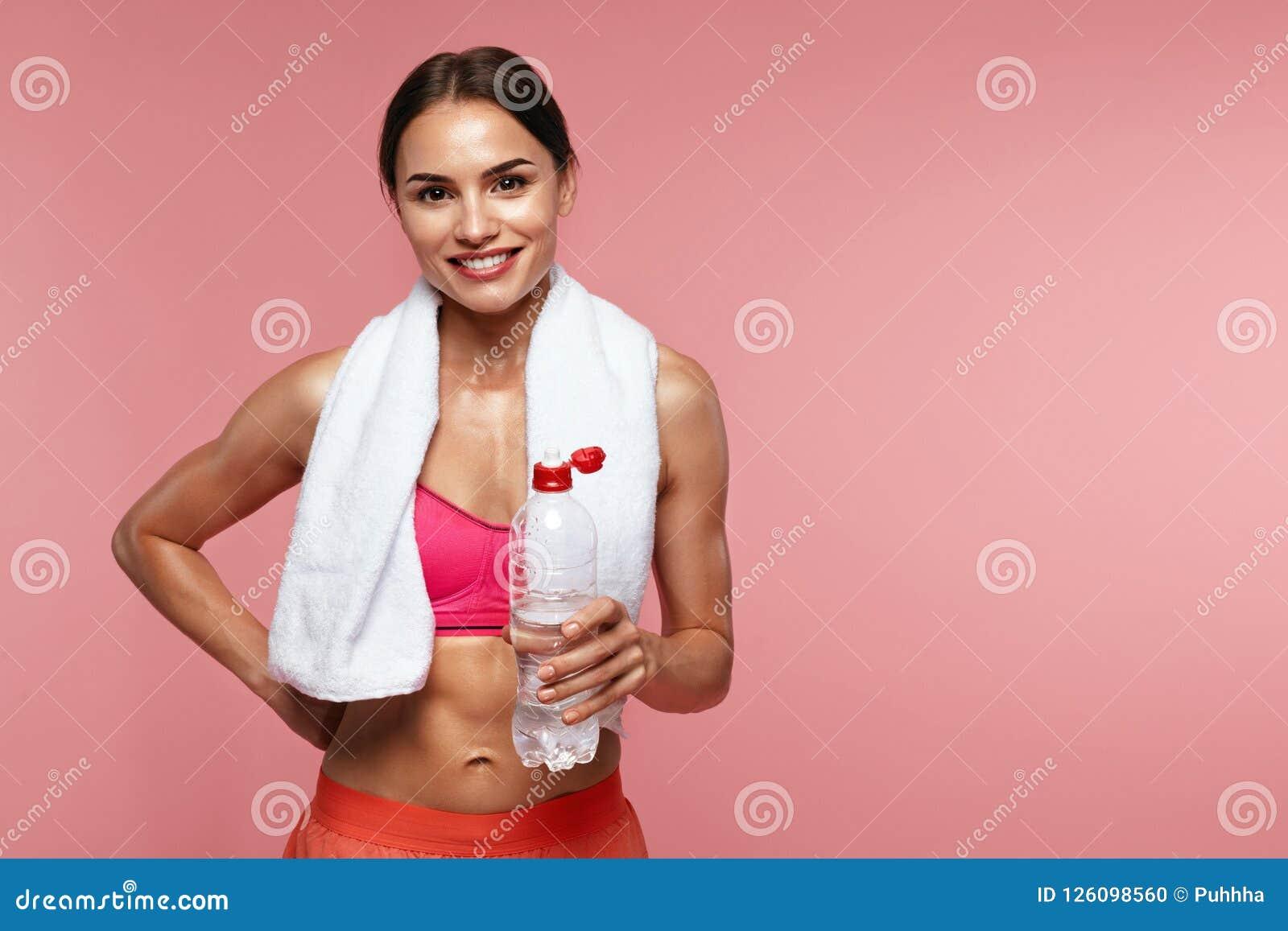 Agua de la bebida Mujer del deporte que sostiene la botella con agua