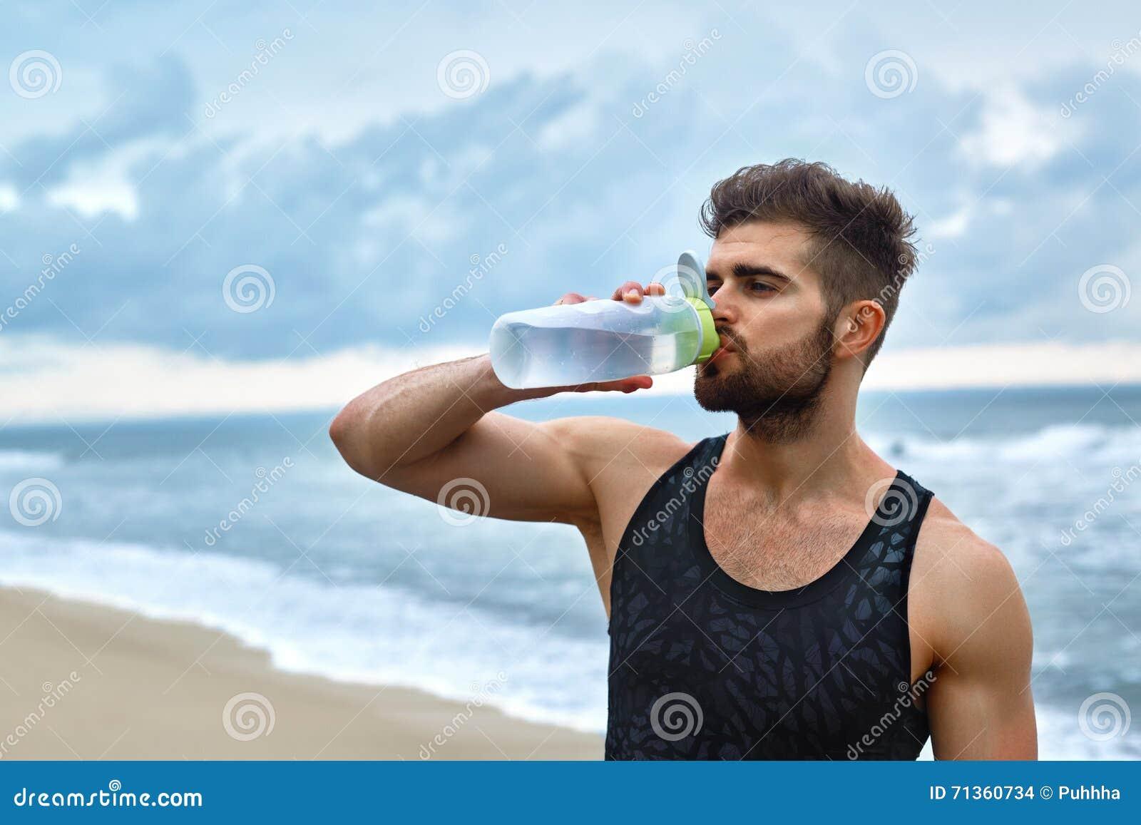 Agua de restauración de consumición del hombre después del entrenamiento en la playa bebida