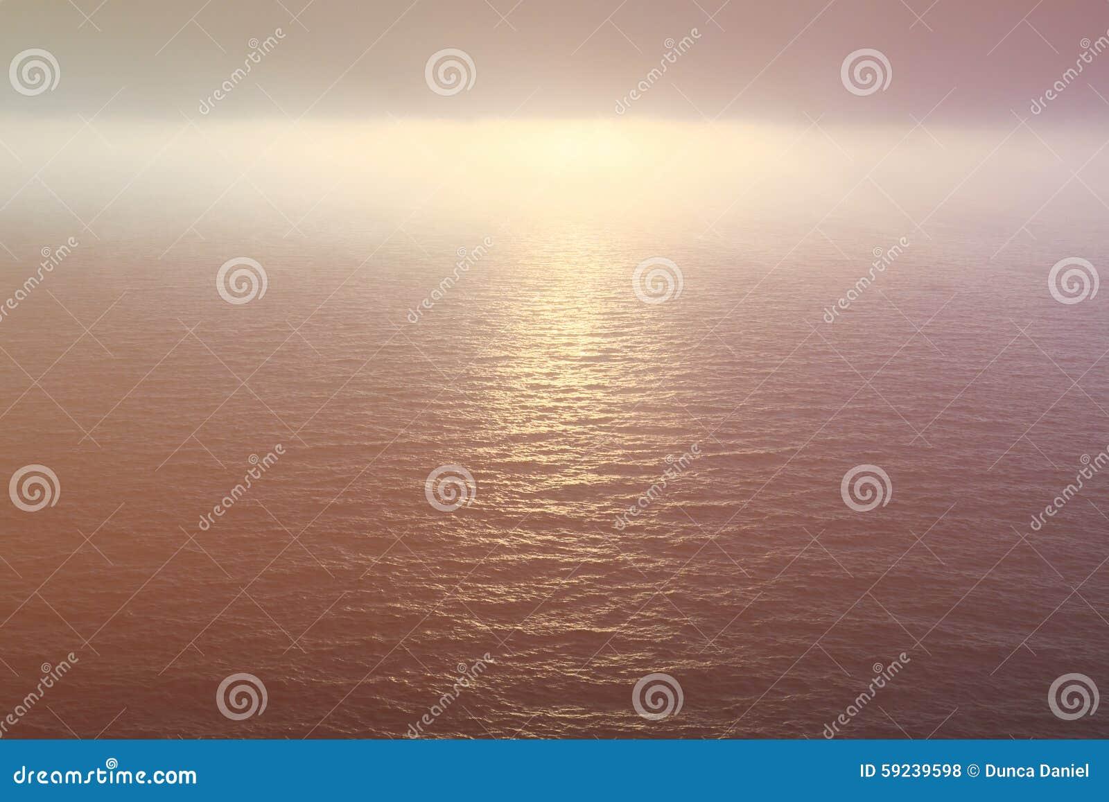 Agua del océano y cielo de niebla en la puesta del sol