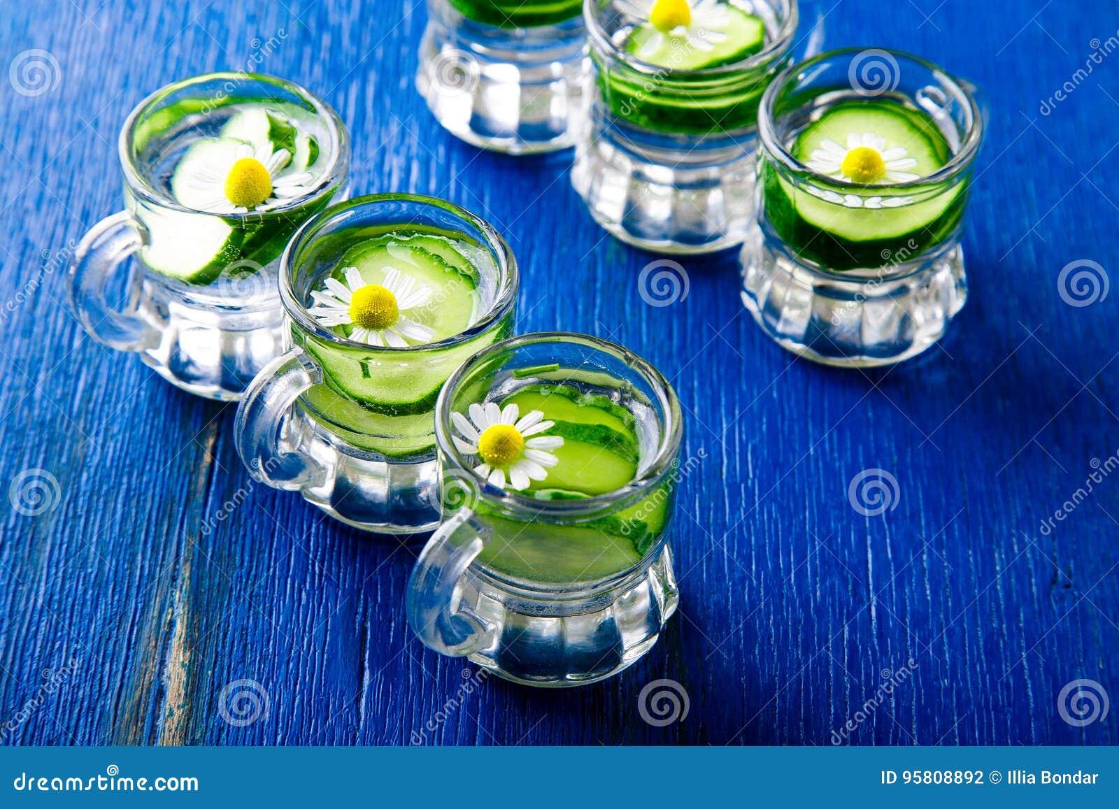 Agua del pepino en seis tarros de cristal del pequeño albañil en fondo azul rústico Detox