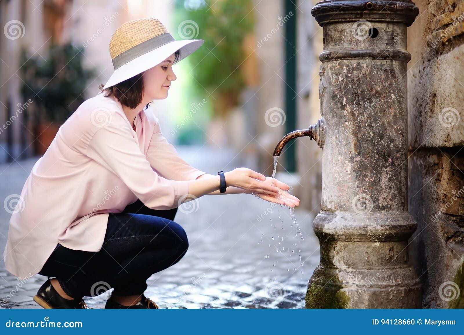 Agua potável bebendo da jovem mulher da fonte em Roma, Itália