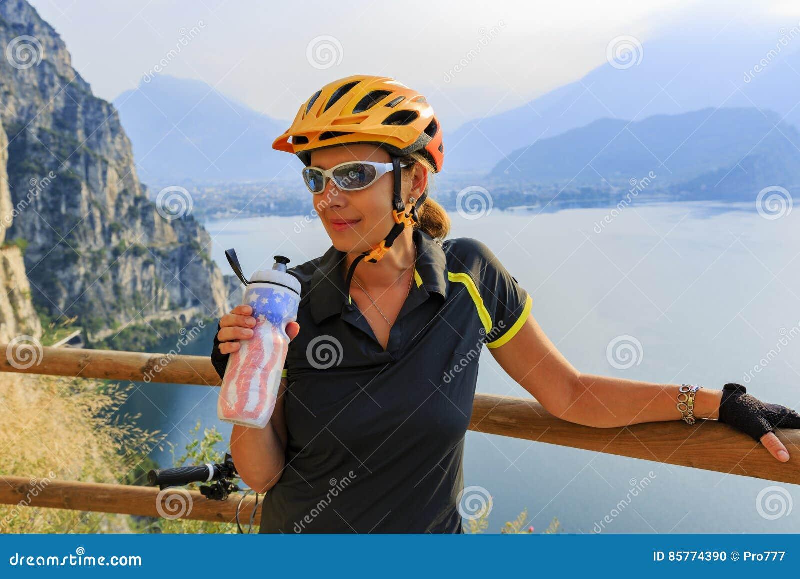 Agua potable biking de la mujer de la montaña
