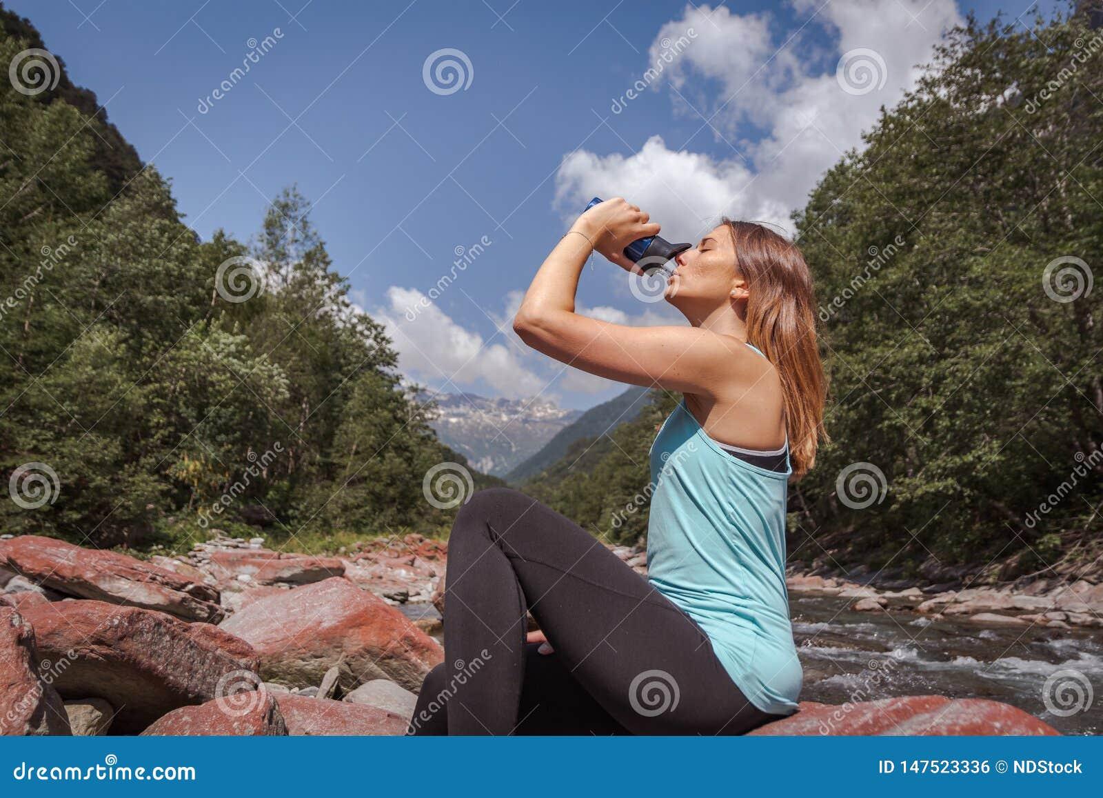 Agua potable de la muchacha y el sentarse en piedra en un río