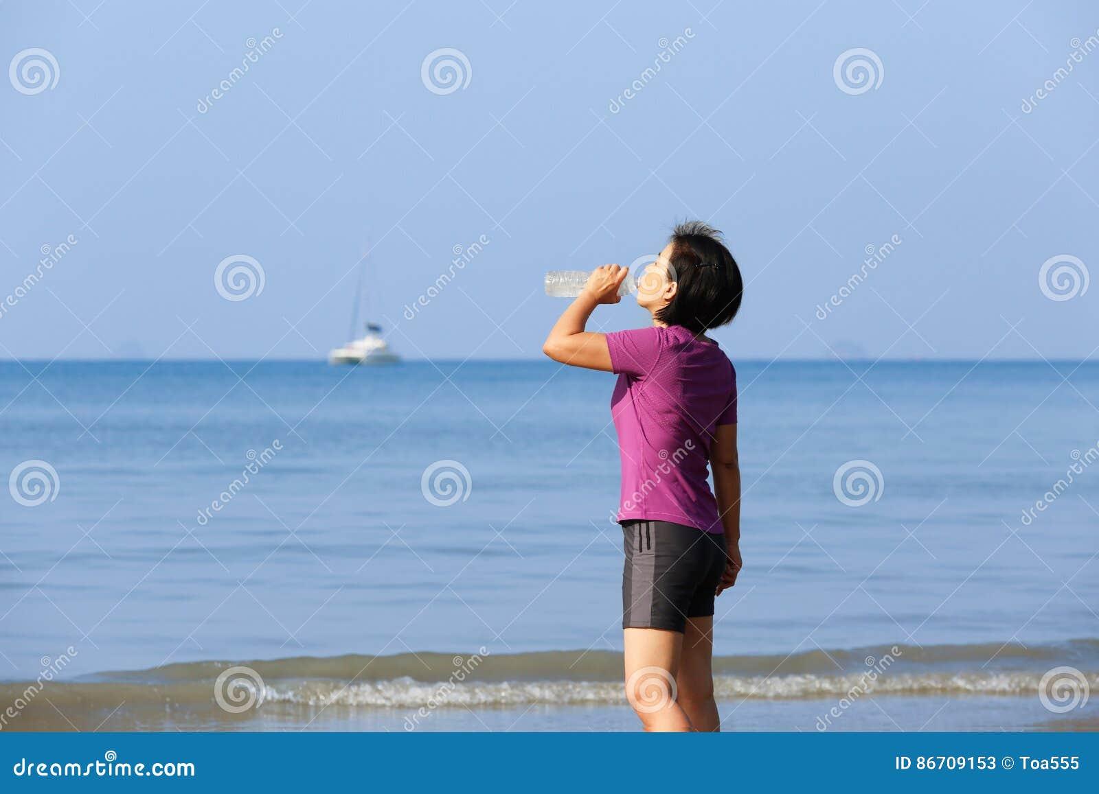 Agua potable de la mujer de la aptitud en la playa, Krabi