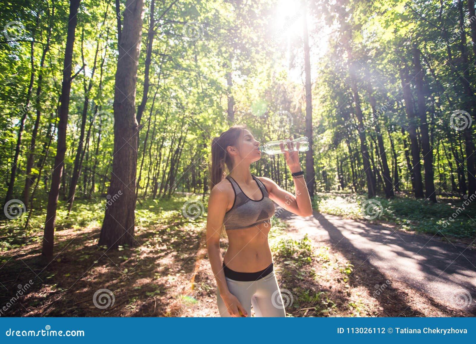 Agua potable de la mujer deportiva al aire libre el día soleado