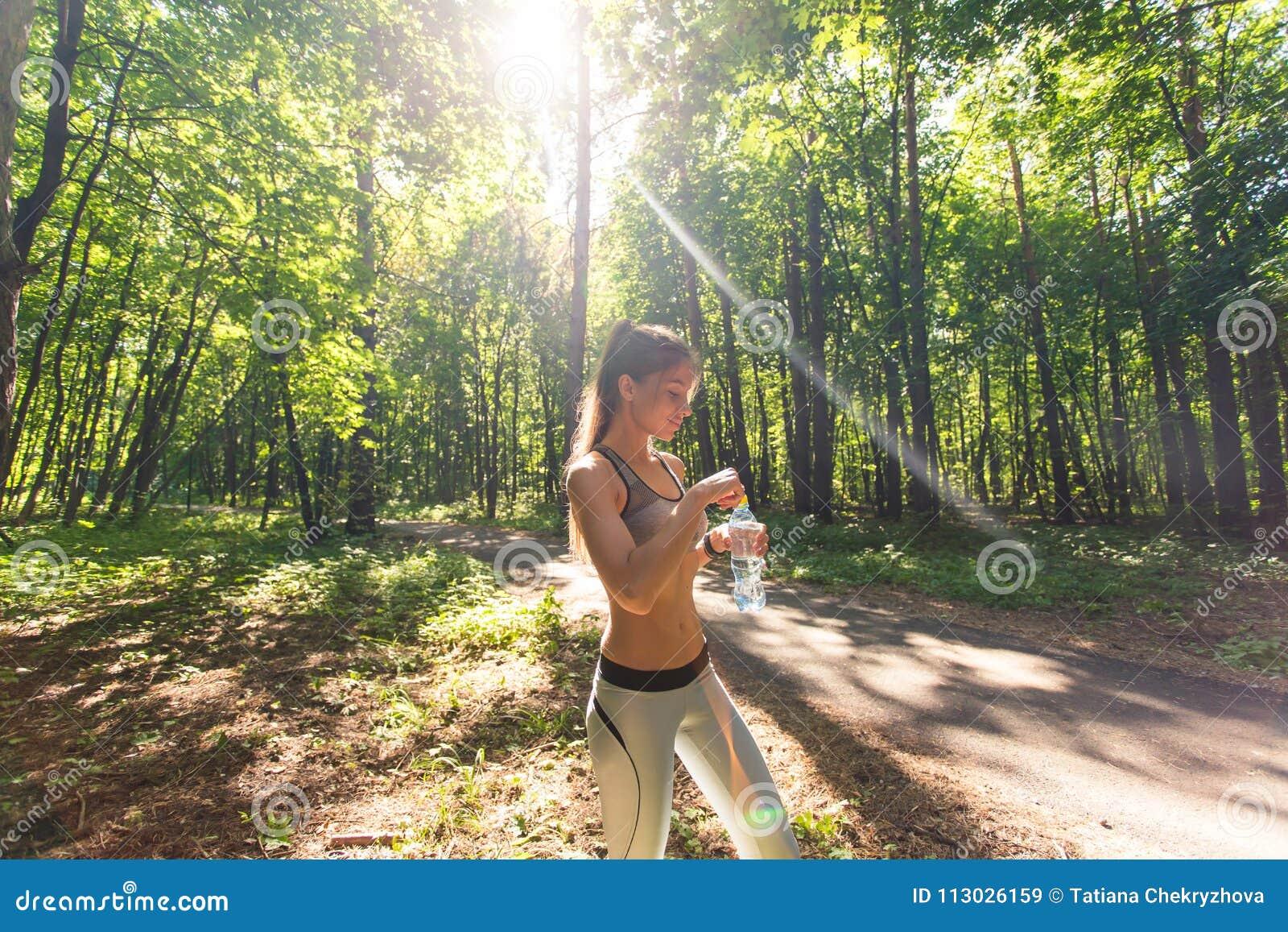 Agua potable de la mujer joven después de activar al aire libre