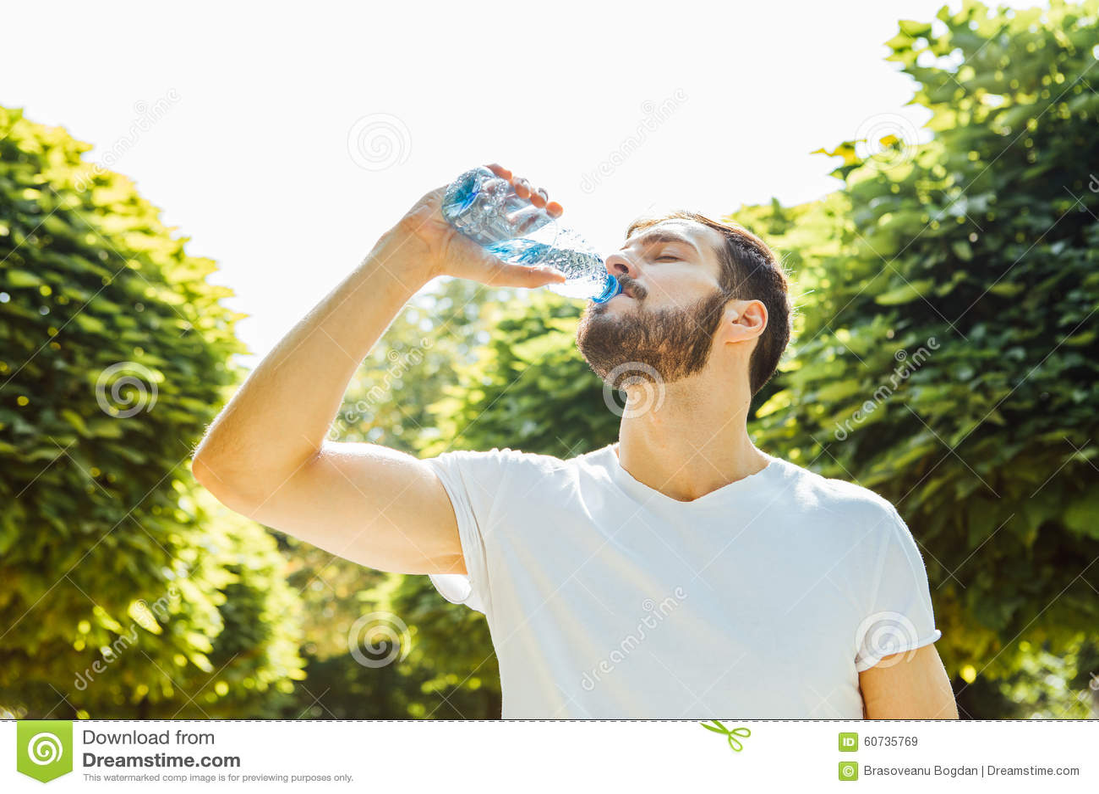 Agua potable del hombre adulto de una botella afuera