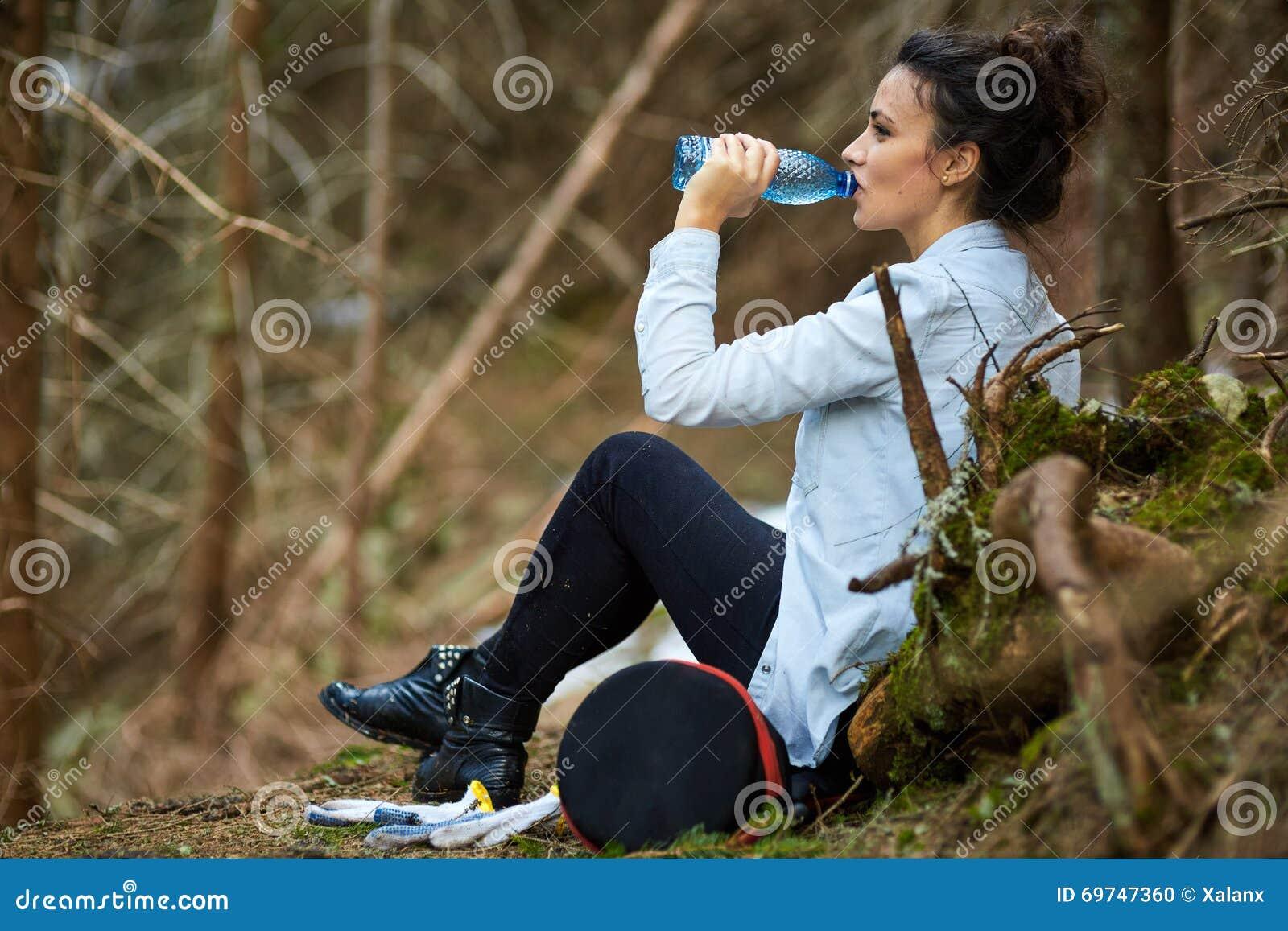 Agua potable del trekker de la mujer en el bosque