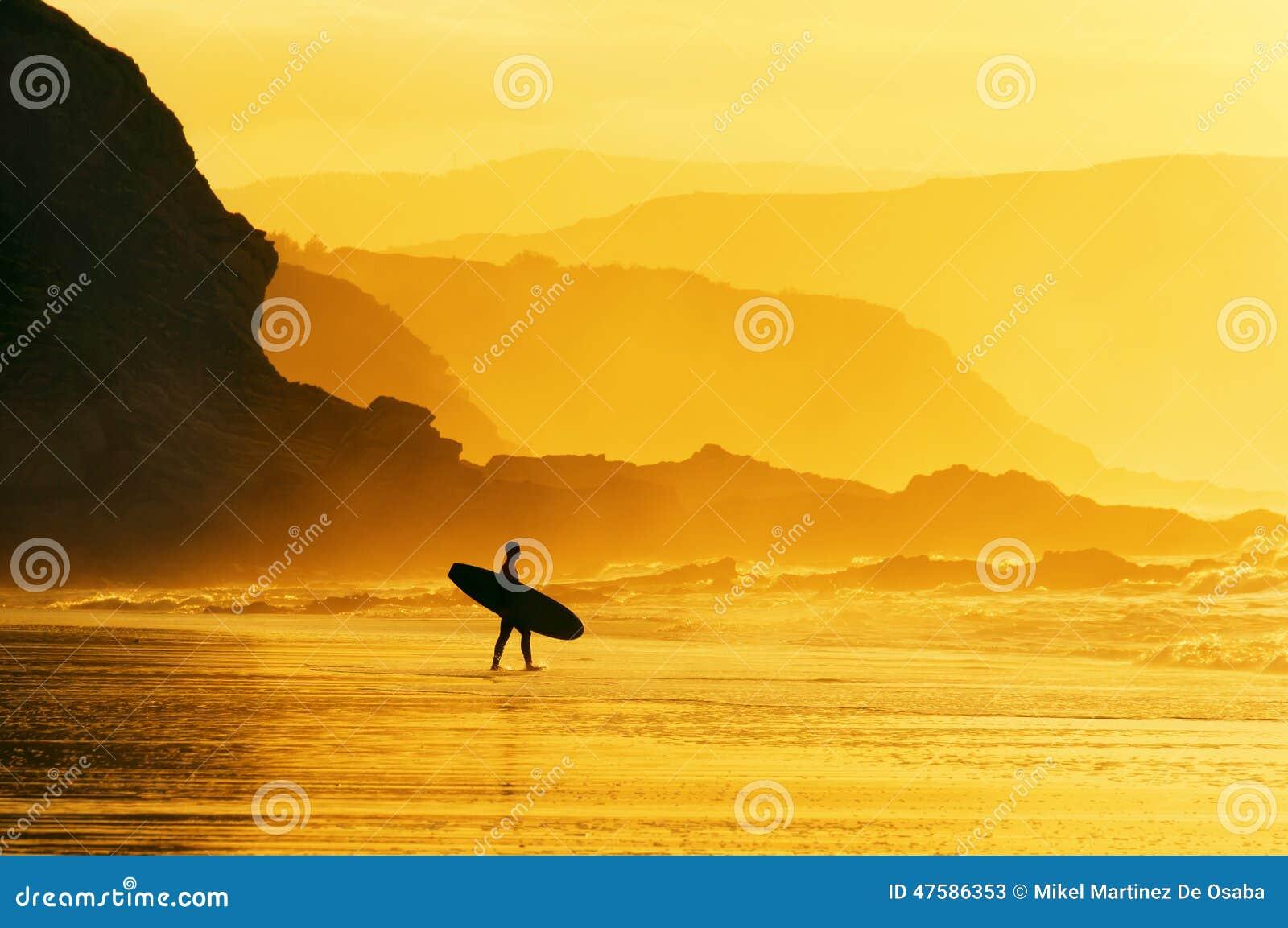 Agua que entra de la persona que practica surf en la puesta del sol brumosa