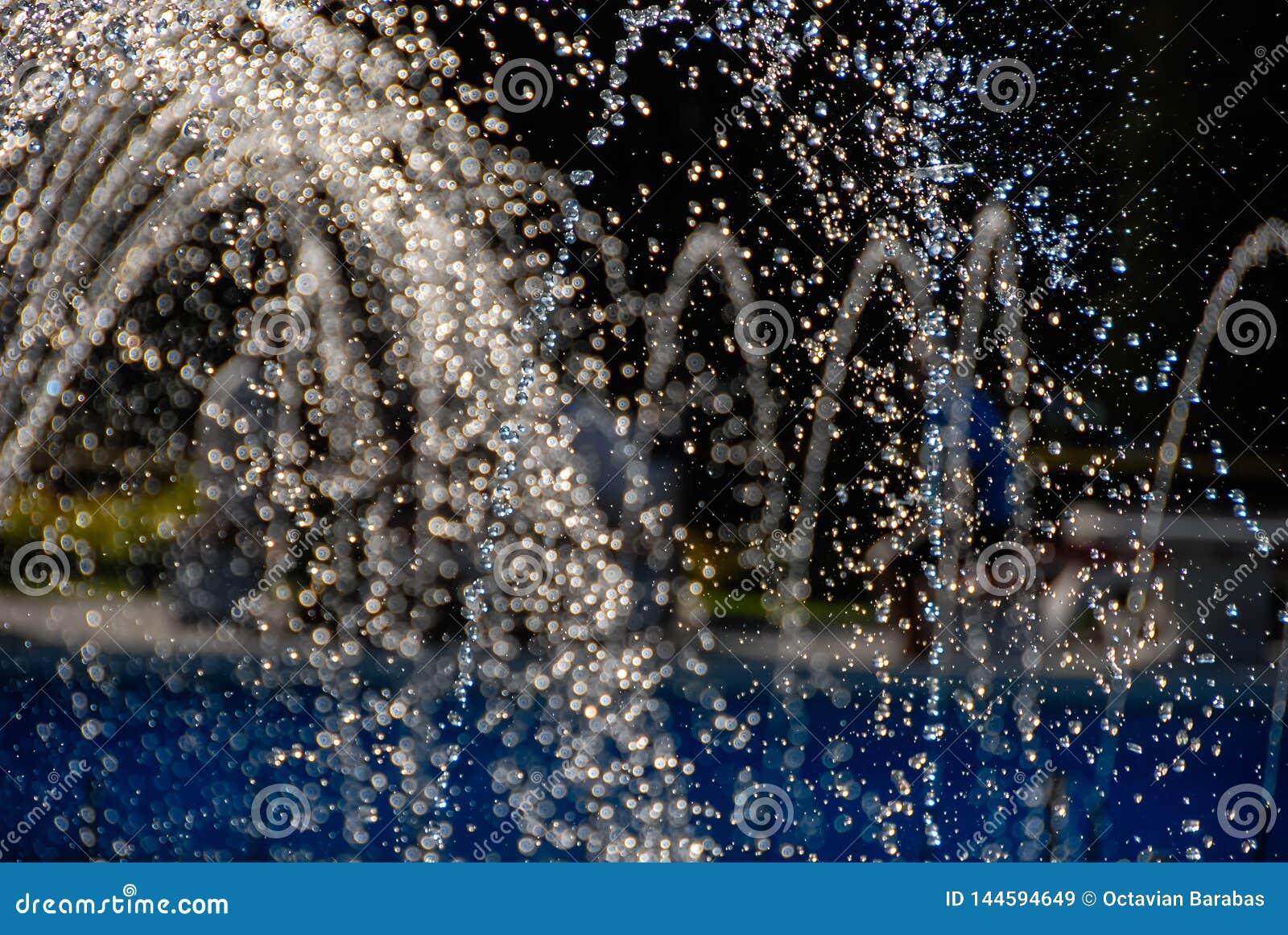Agua que fluye de una fuente que forma gotitas