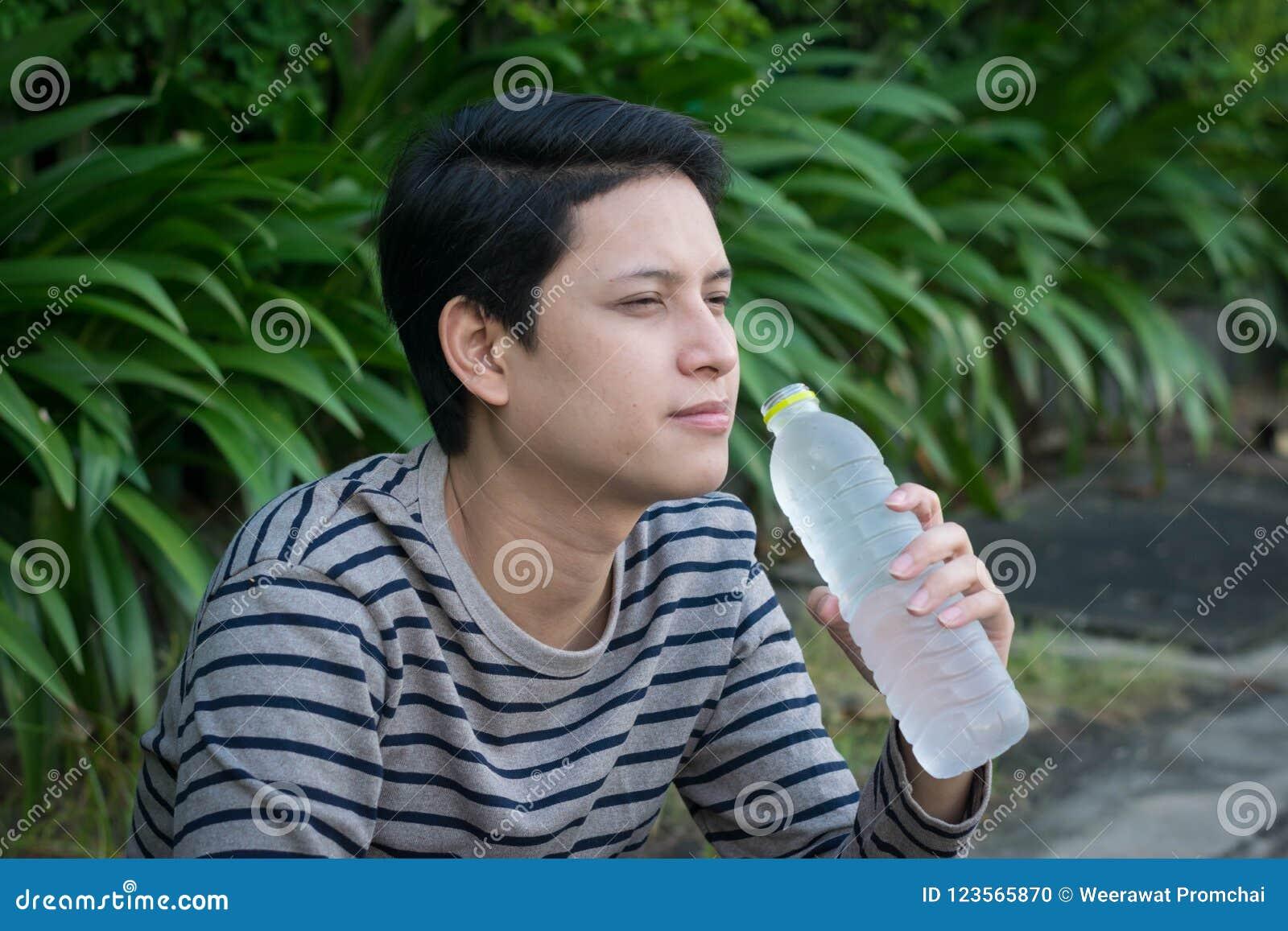 Agua que se sienta y potable del hombre asiático