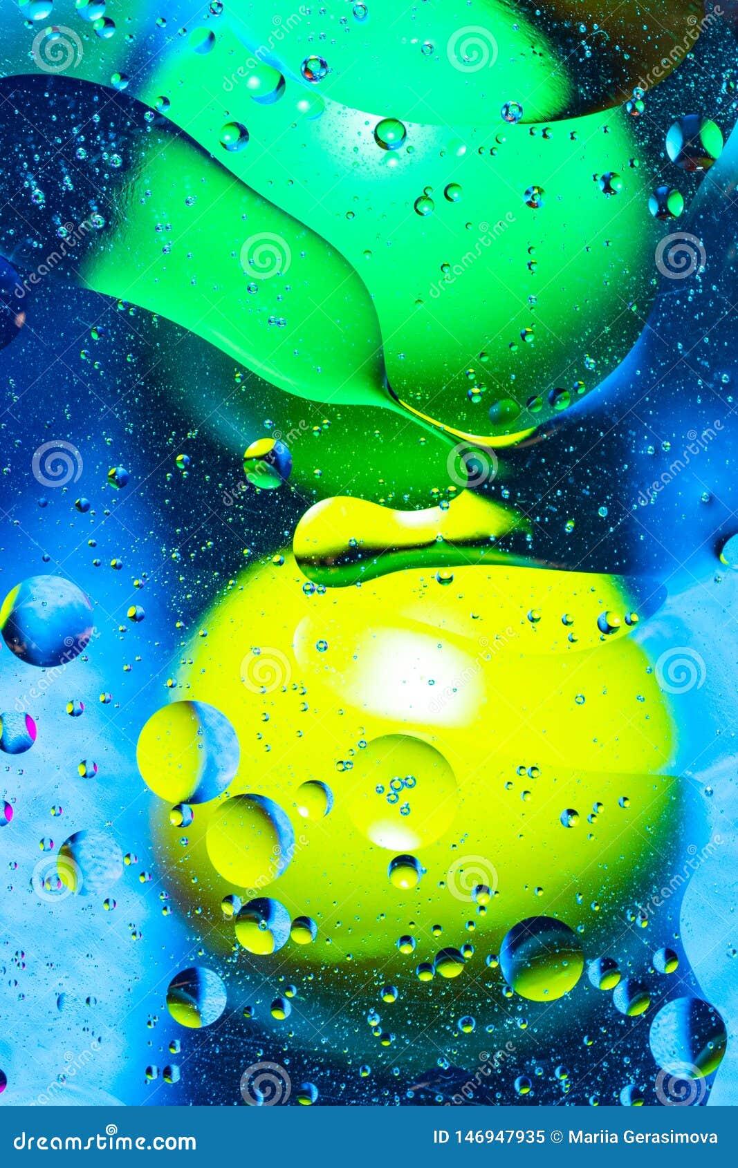 Agua y aceite de mezcla en c?rculos y ?valos abstractos de las bolas del color hermoso de una pendiente del fondo