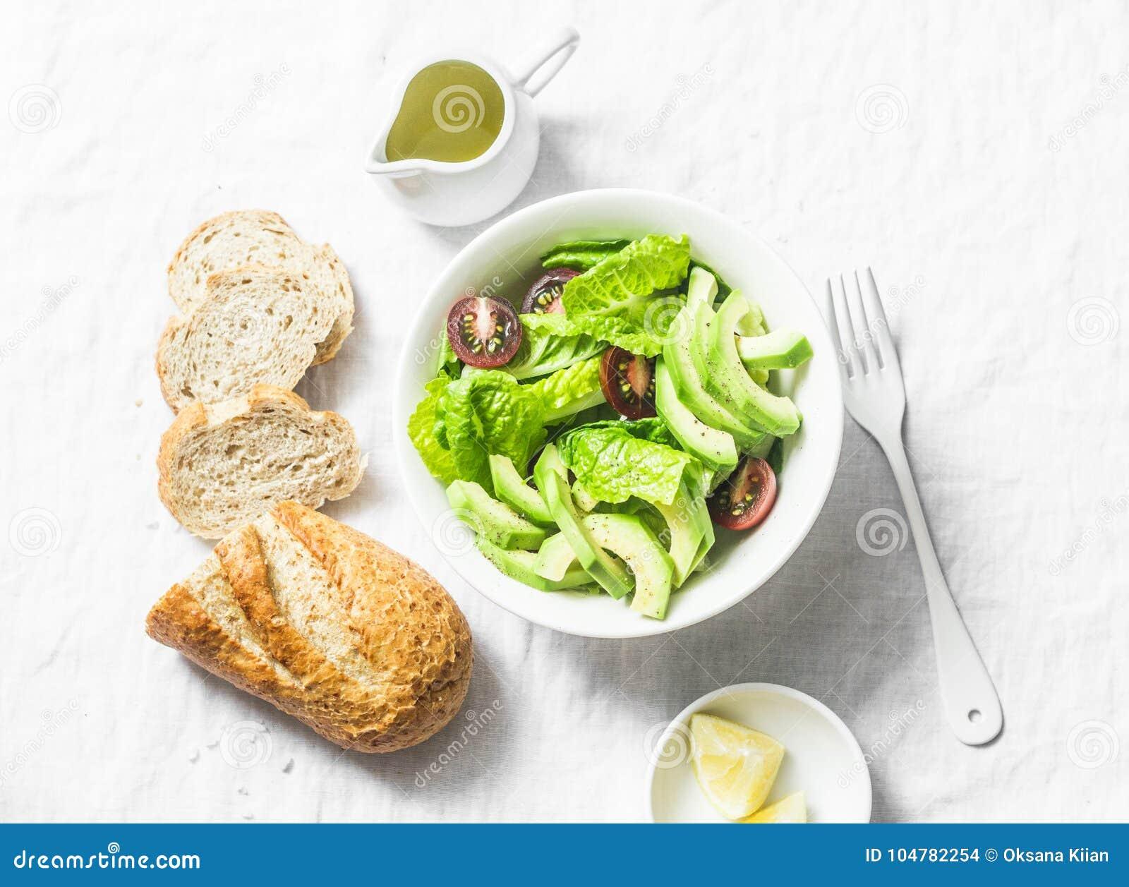 Aguacate, romano, tomates ensalada del kumato y pan branny del trigo integral en el fondo ligero, visión superior Comida del vege
