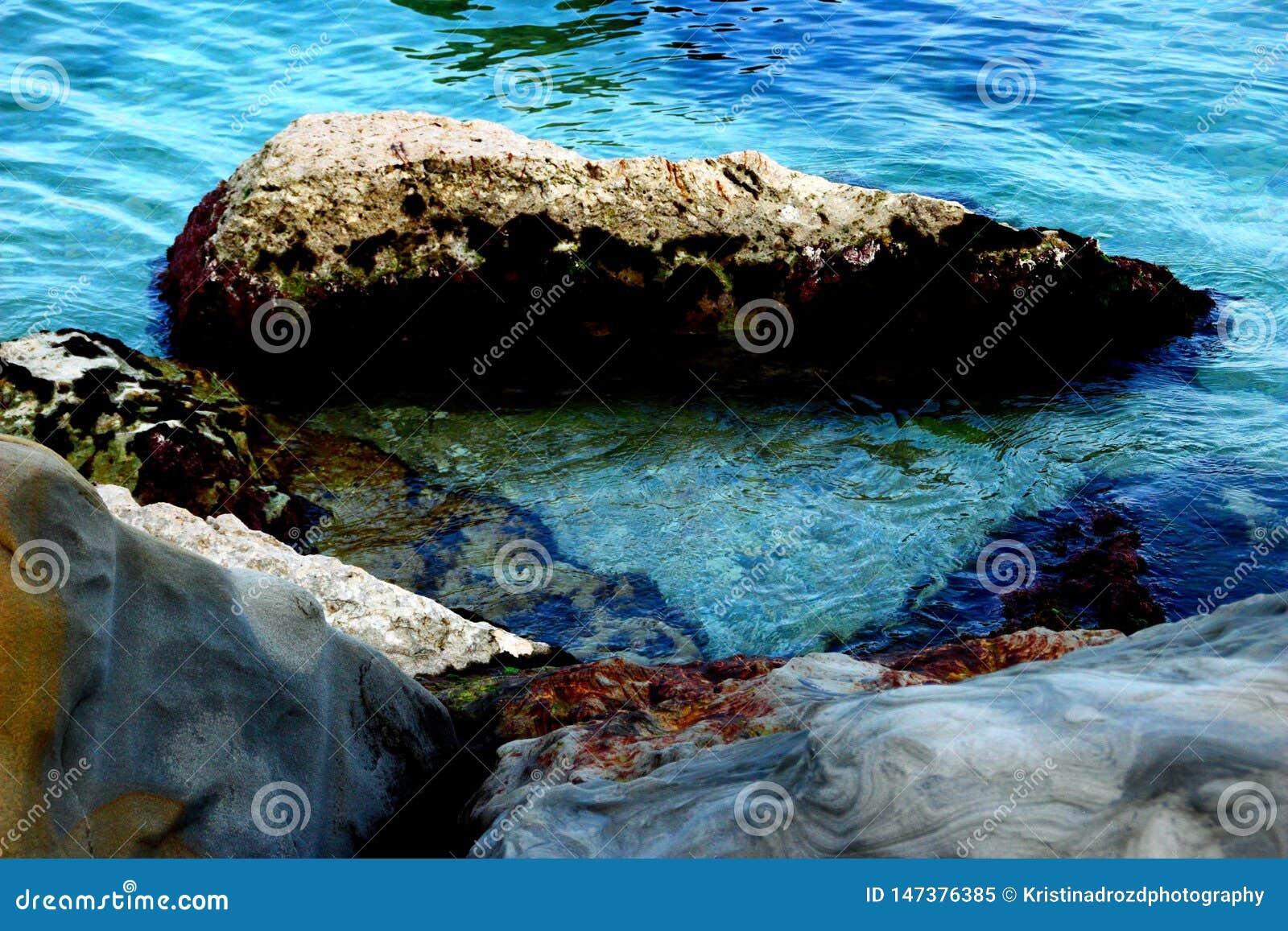 Aguas transparentes del mar adriático que lava algunas piedras