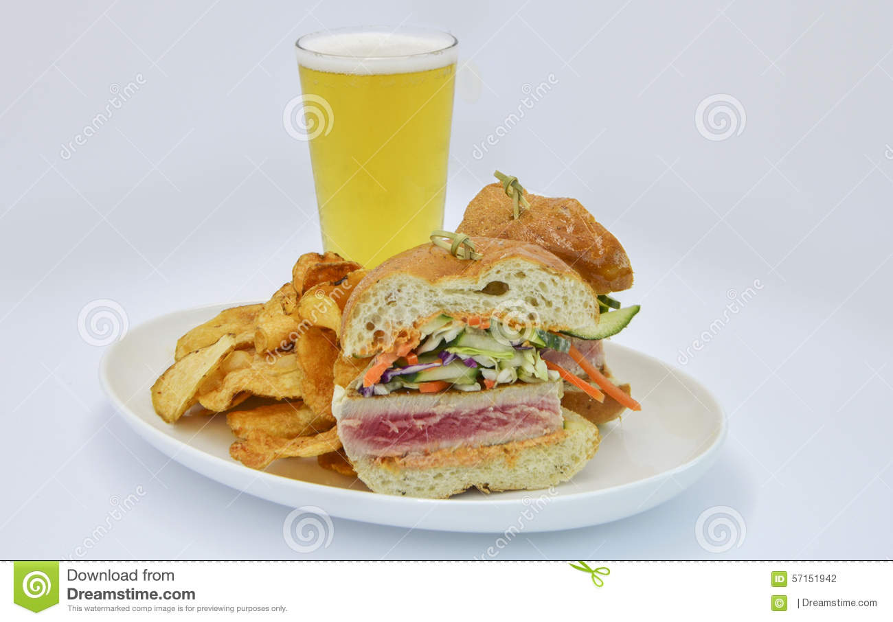 Fresh Ahi Tuna sandwich with potato chips and beer.